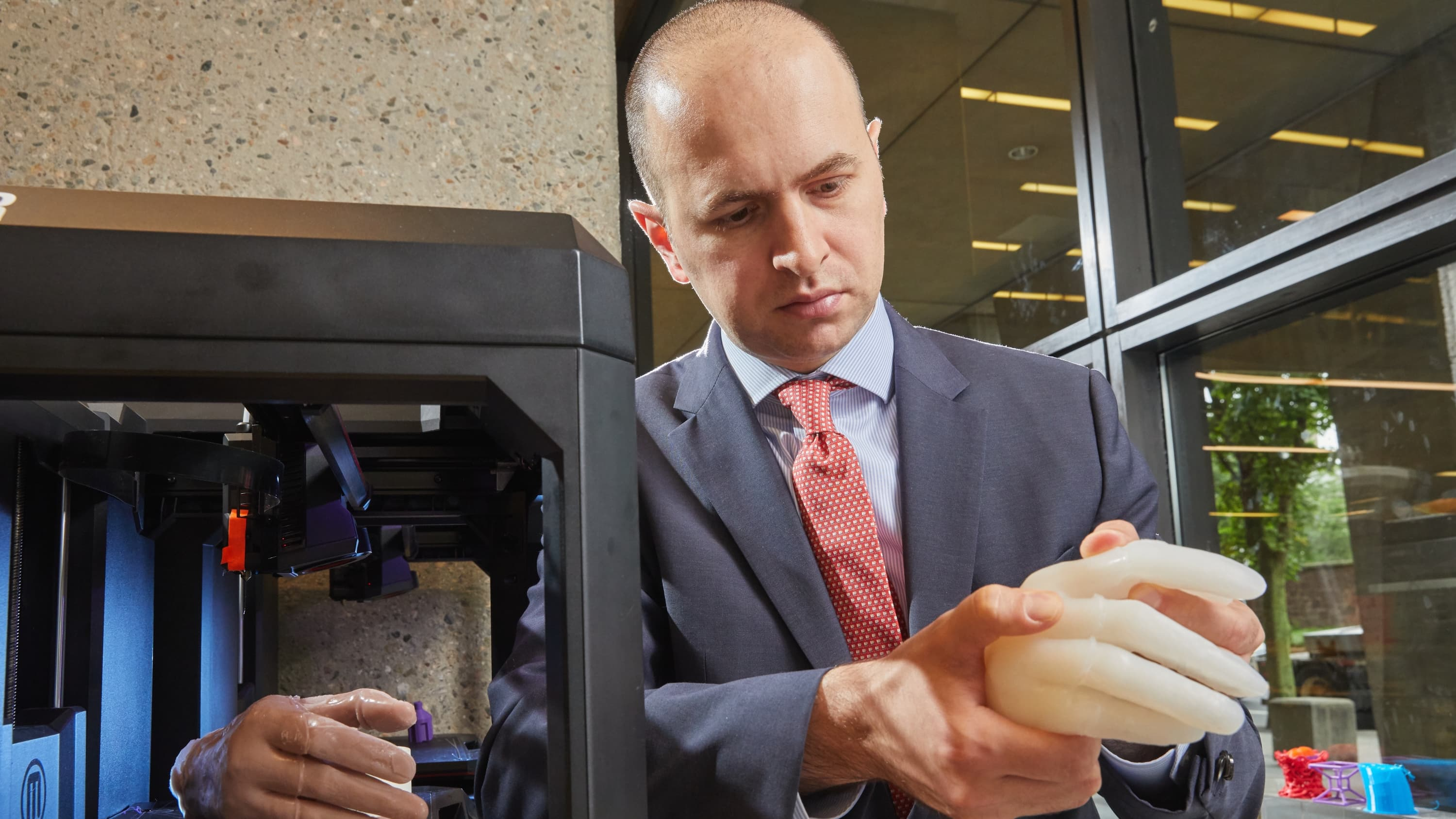 Dr. Adnan Prsic holding a 3D-printed model of a hand