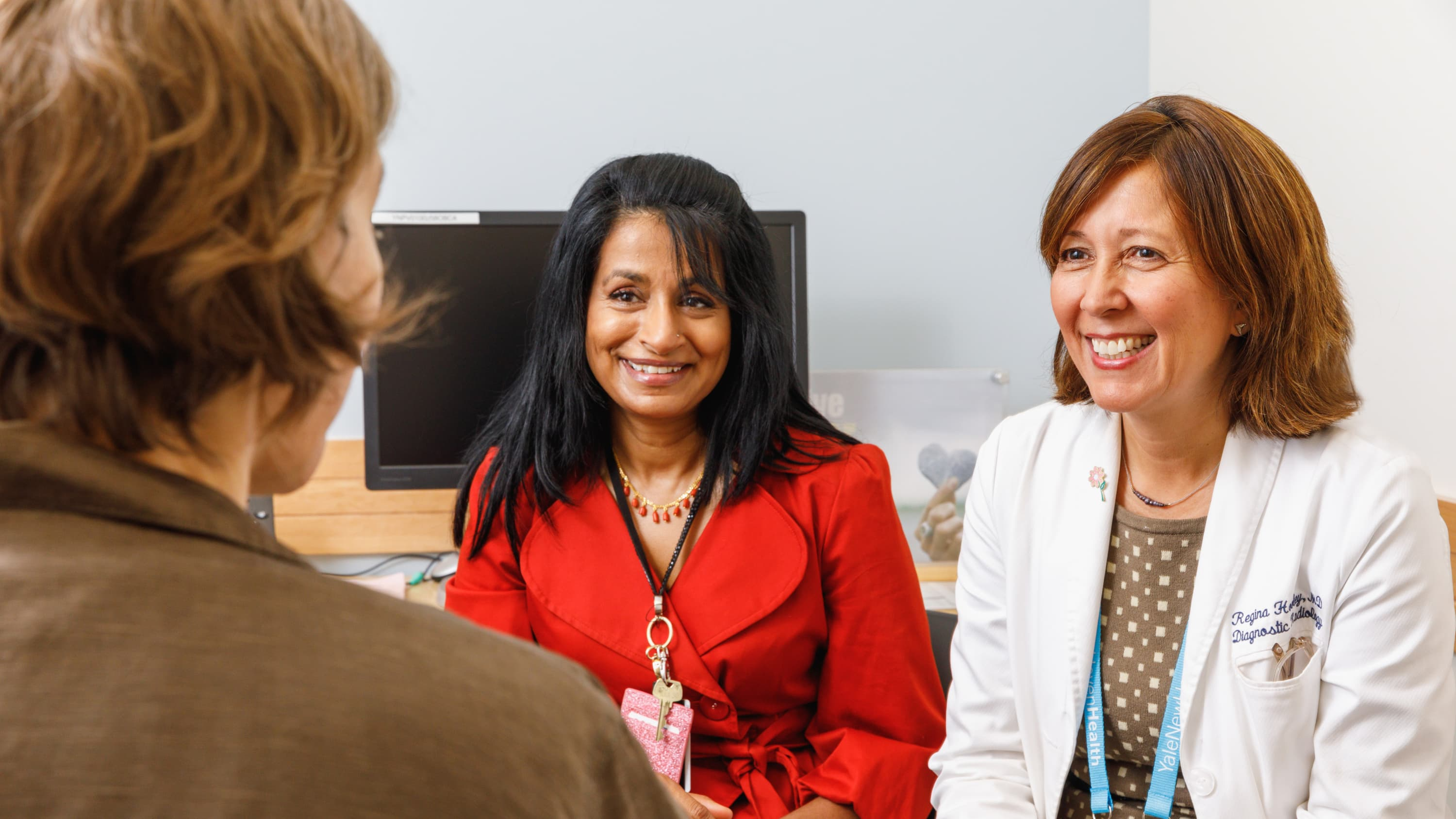 Dr.  Moran (left) and Dr. Hooley (right) consult with a patient.