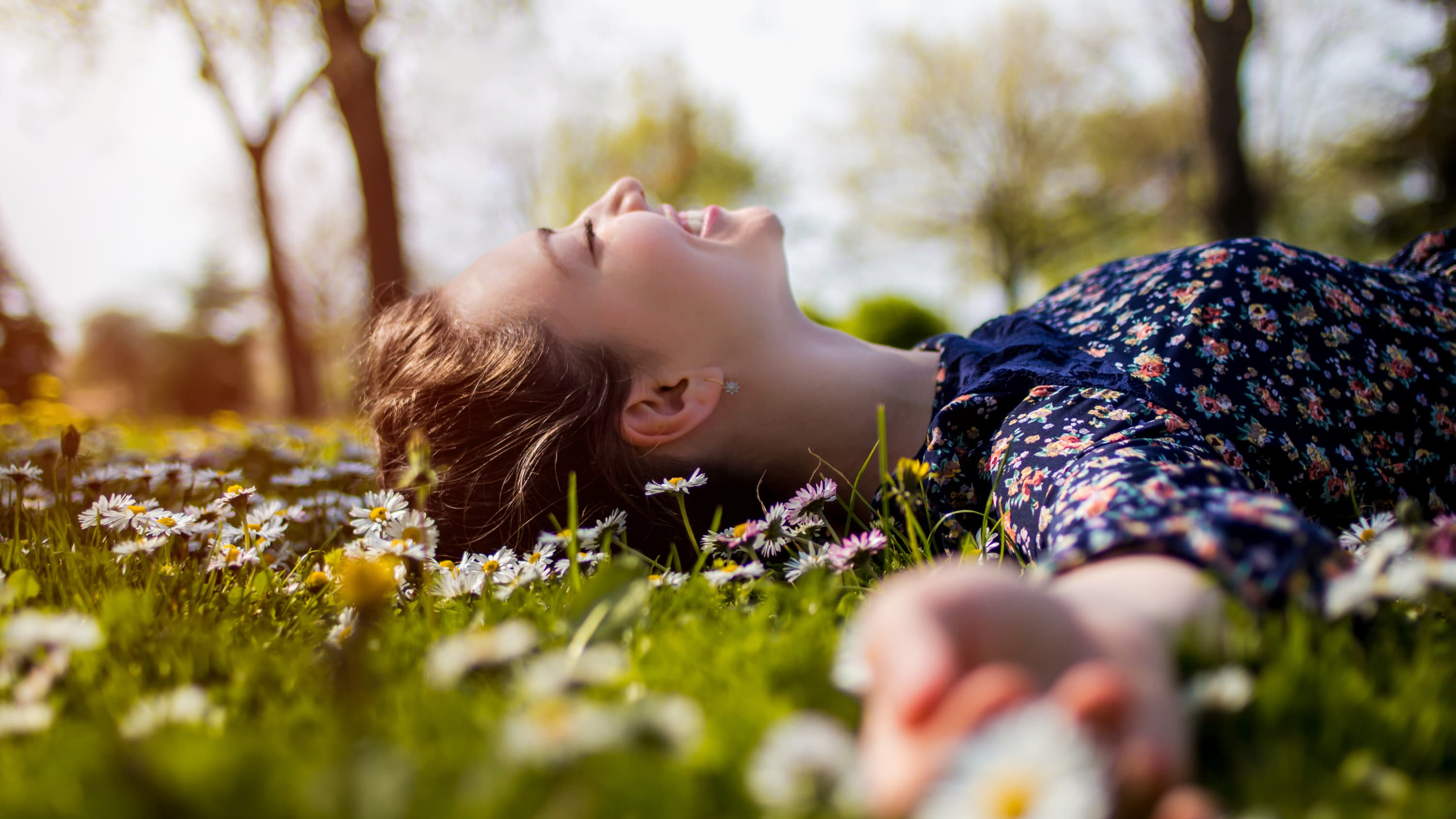 happy teenager lying in grass, possibly because of promising trial results for the Pfizer-BioNTech vaccine in adolescents