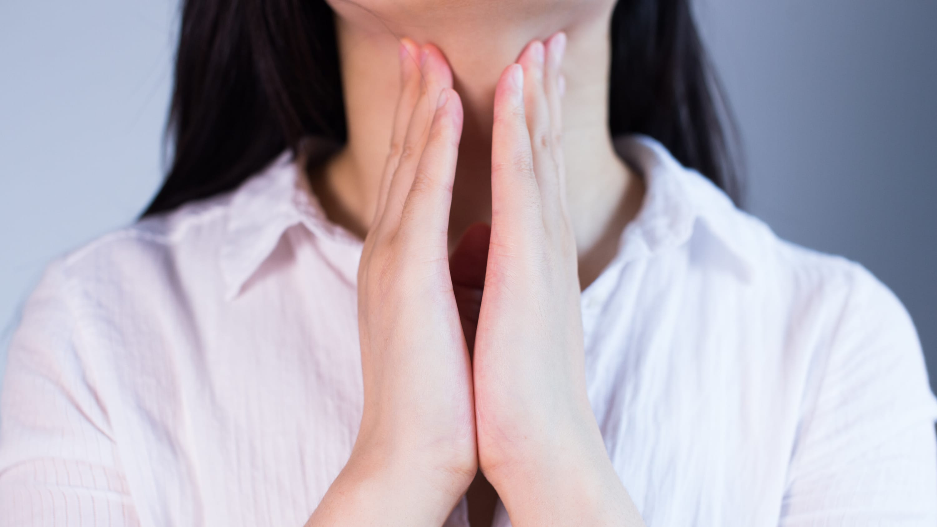 A woman concerned about thyroid cancer touches her thyroid, she is wearing a blouse her face is not visible.