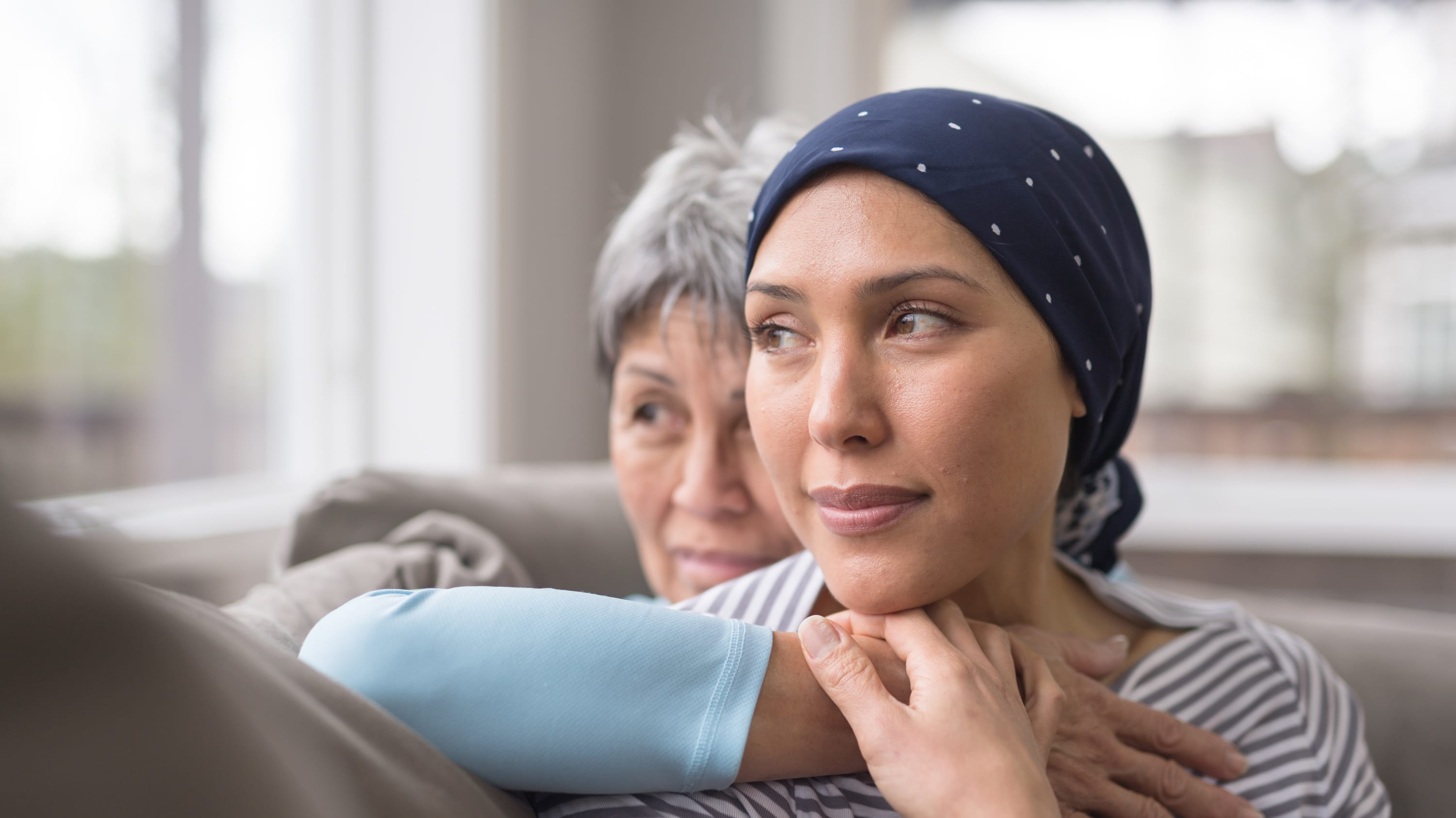 older woman holding younger woman, who has breast cancer