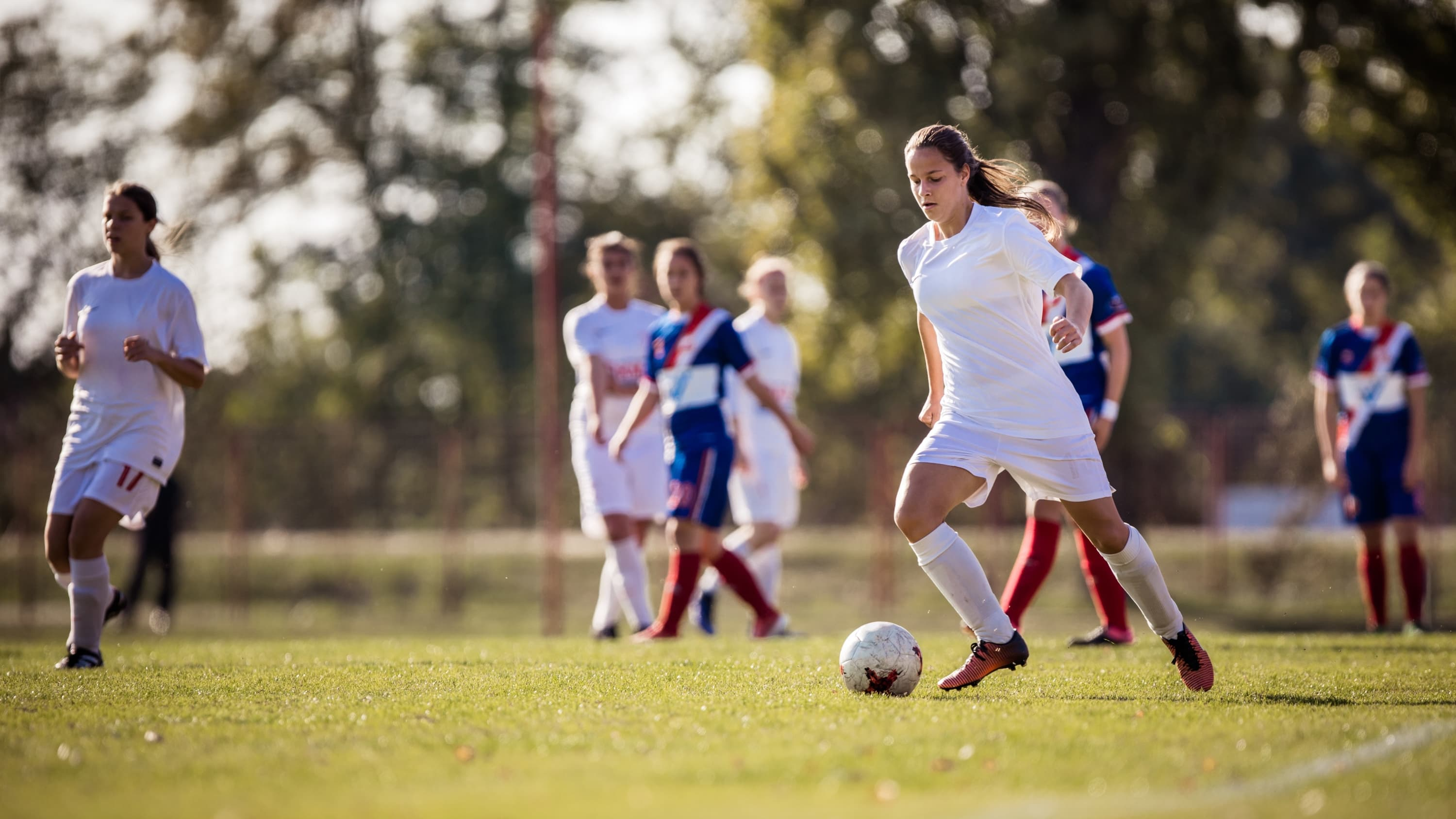 female soccer player, dribbling soccer ball, possibly before an injury to articular cartilagge