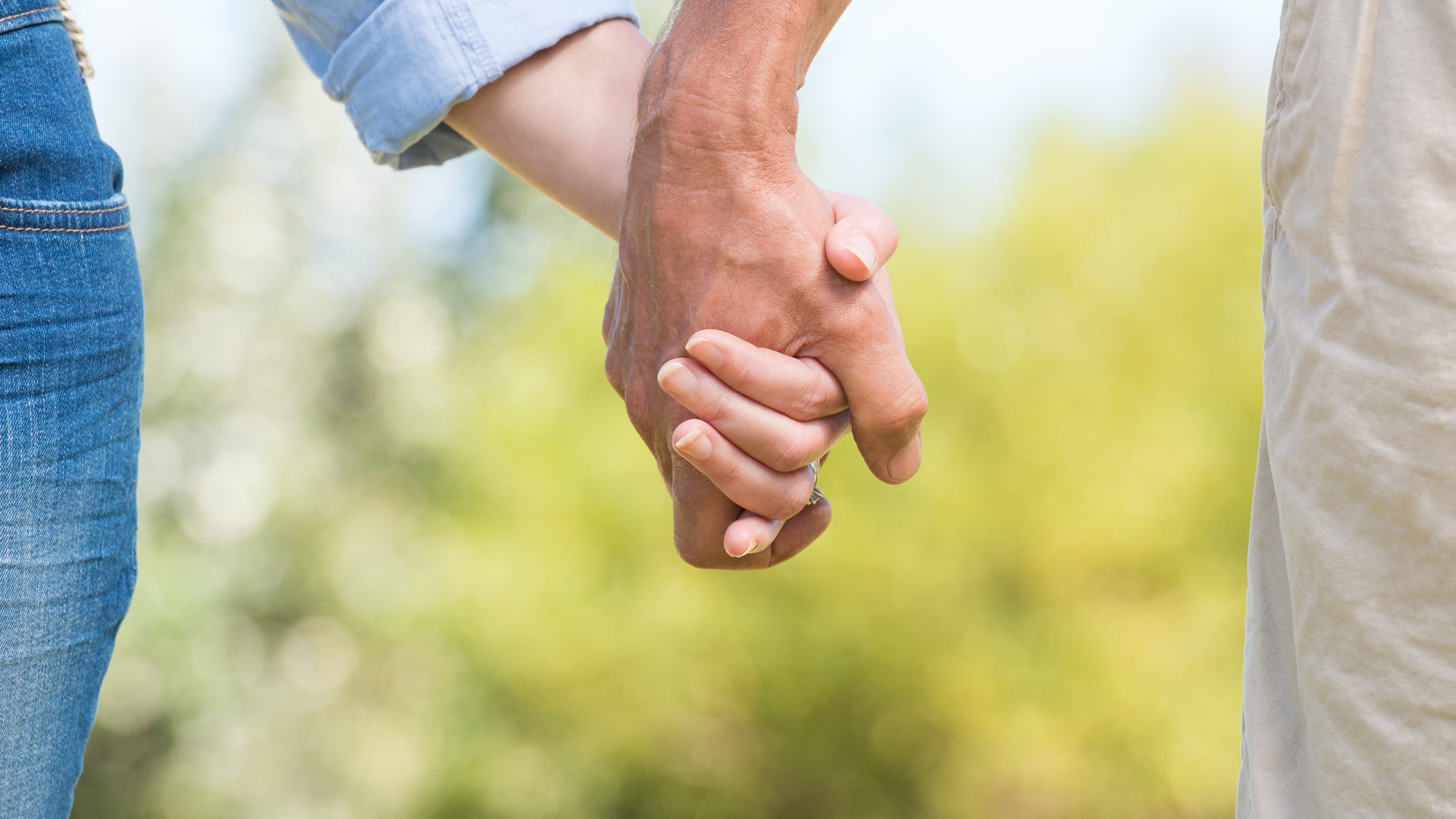 A close up image of two people holding hands, just the hands, in hopes of avoiding a sexually transmitted infection.