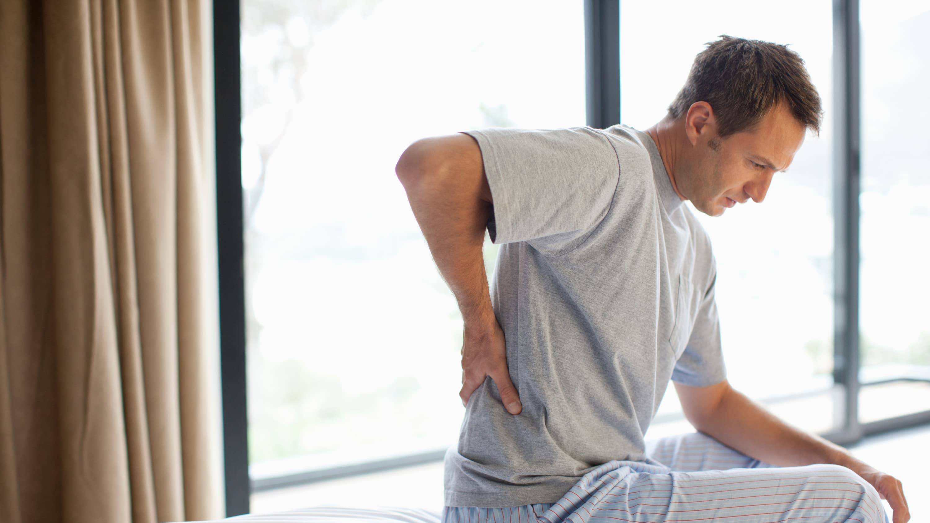 A man sits on his bed, rubbing his back, possibly from a herniated disc