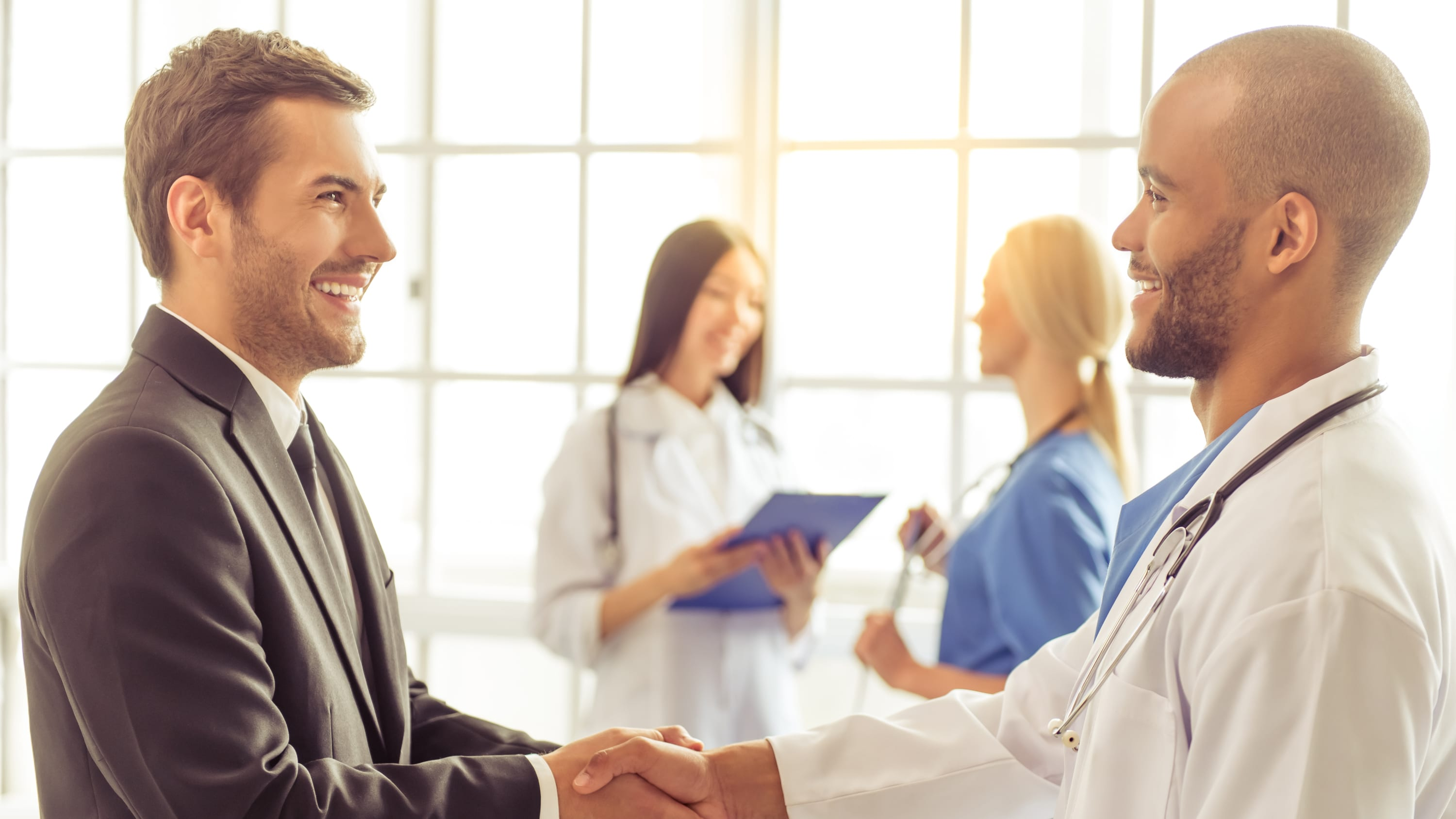 A volunteer for a clinical trial shakes a doctor's hand.