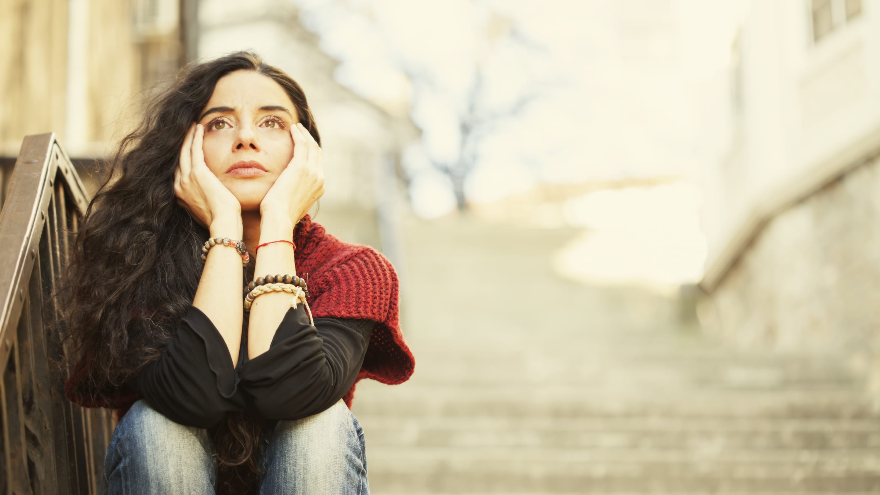 A woman sits on concrete steps, thinking, possibly about pelvic organ prolapse