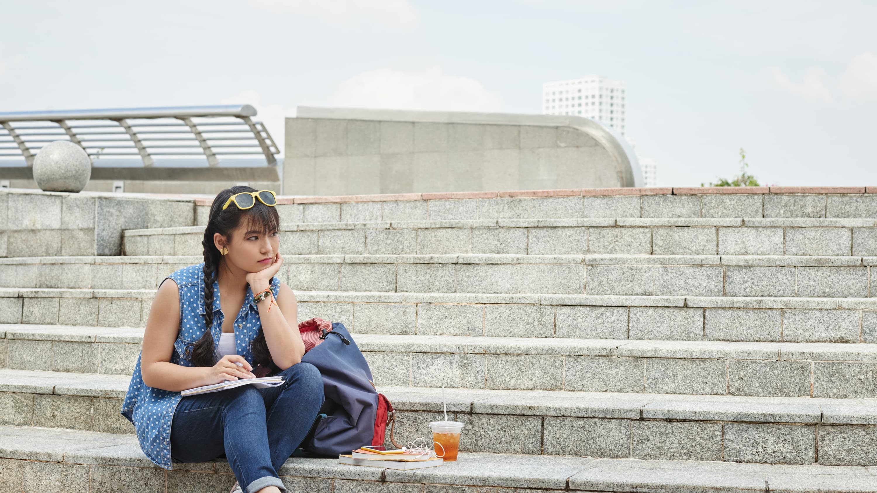 A young woman sits outside on stairs, possibly concerned about sarcoma
