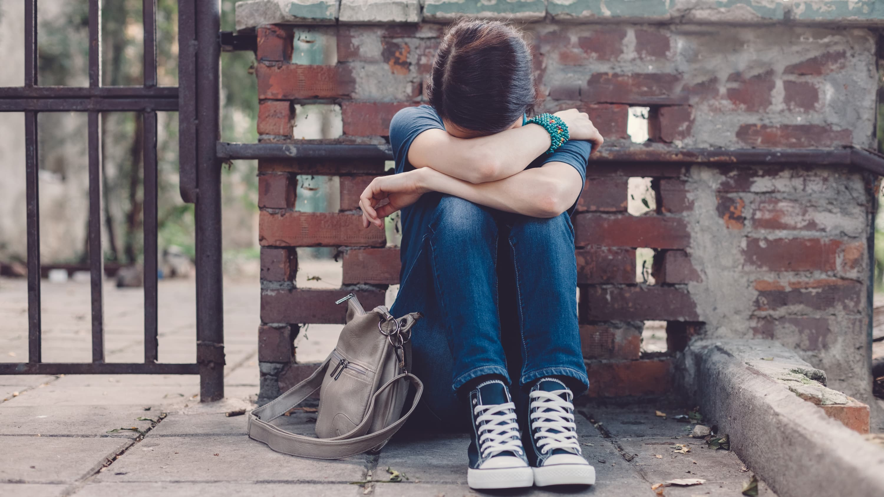 A boy who looks like he is feeling depressed sits on the ground beside his backpack with his head in his hands.
