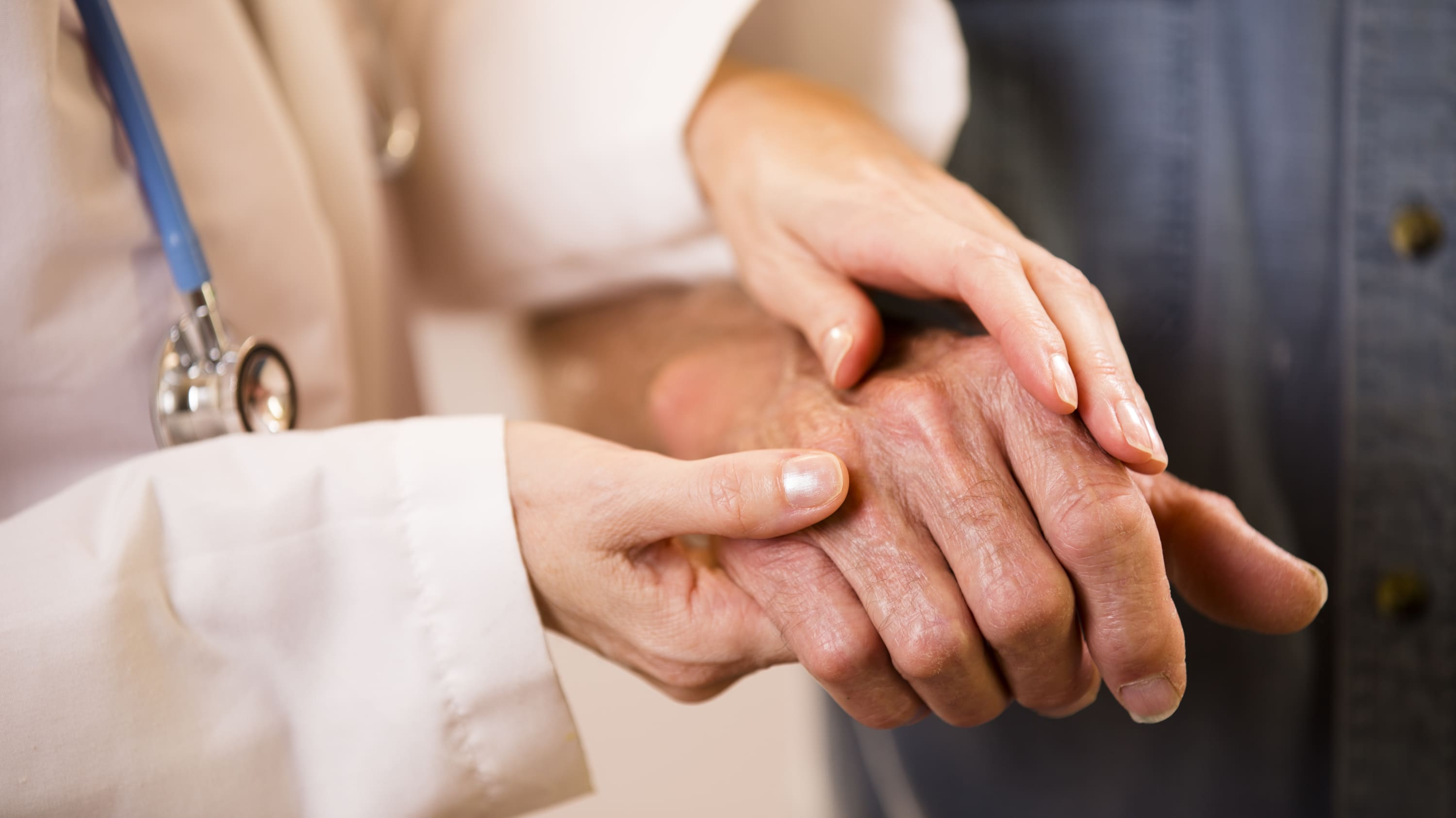 A woman touches a man's hands, someone who possibly has rheumatoid arthritis