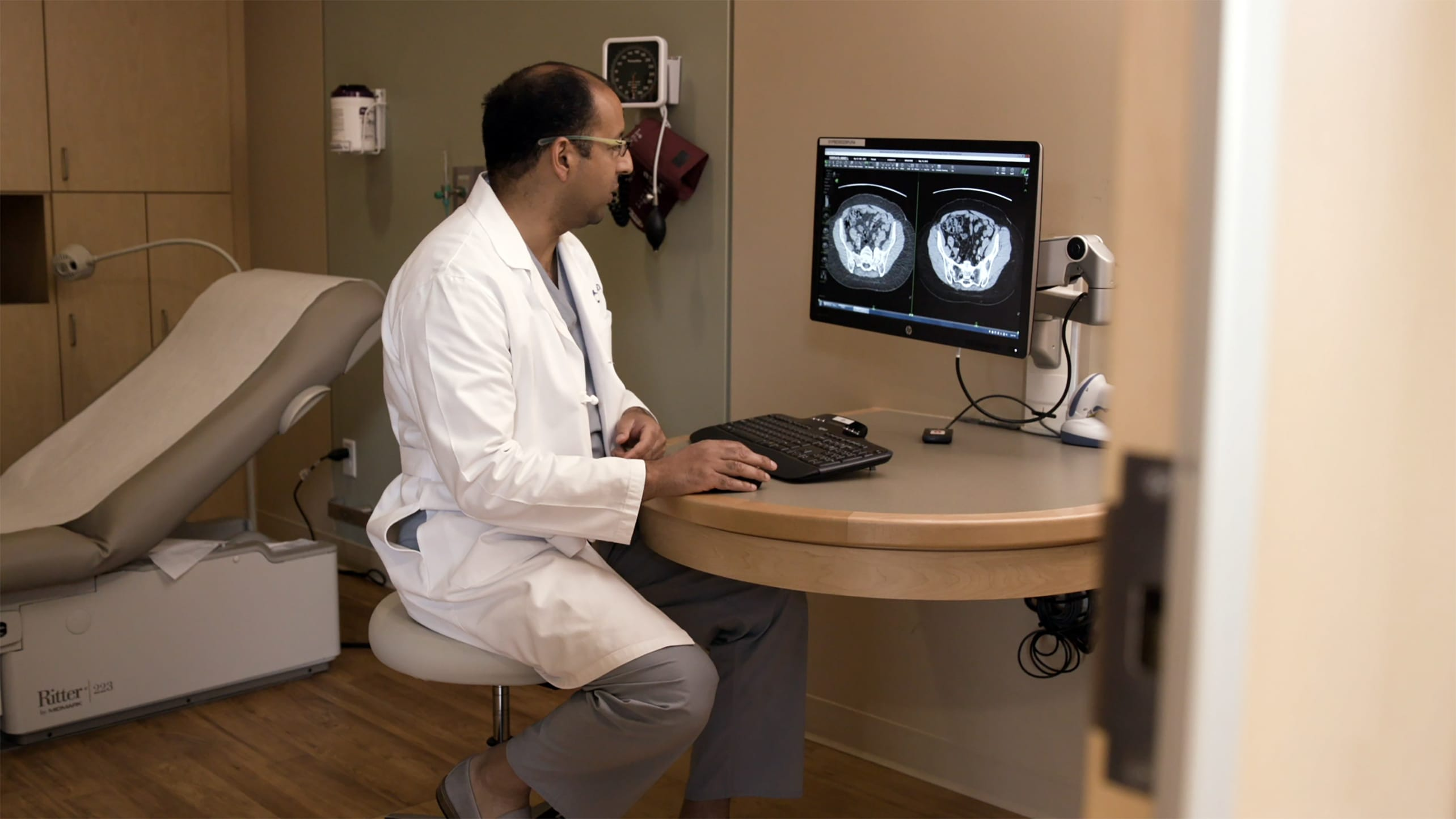 A doctor examines two different types of CT scans in a clinic.