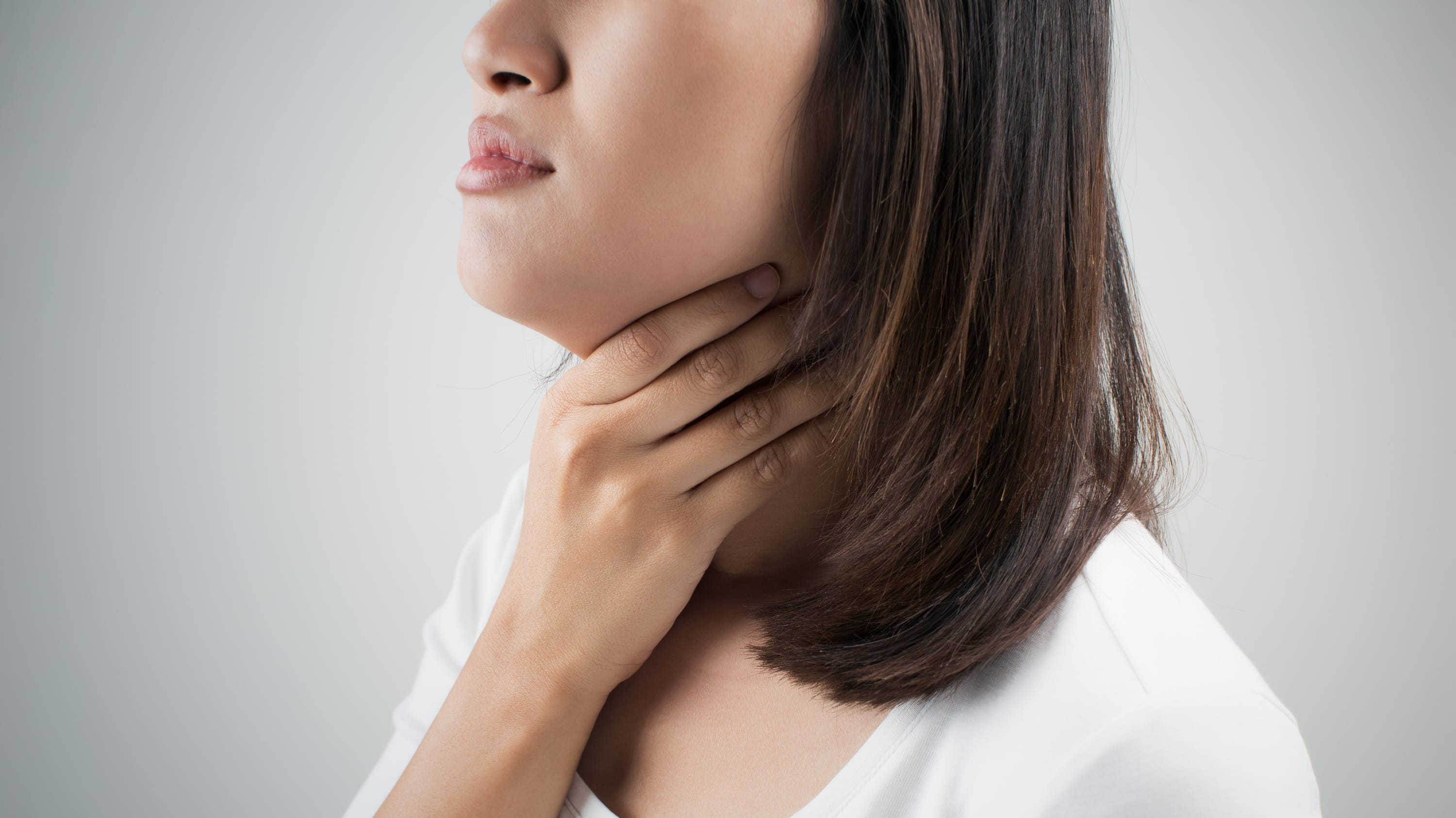 A woman with a thyroid disorder holds her throat.