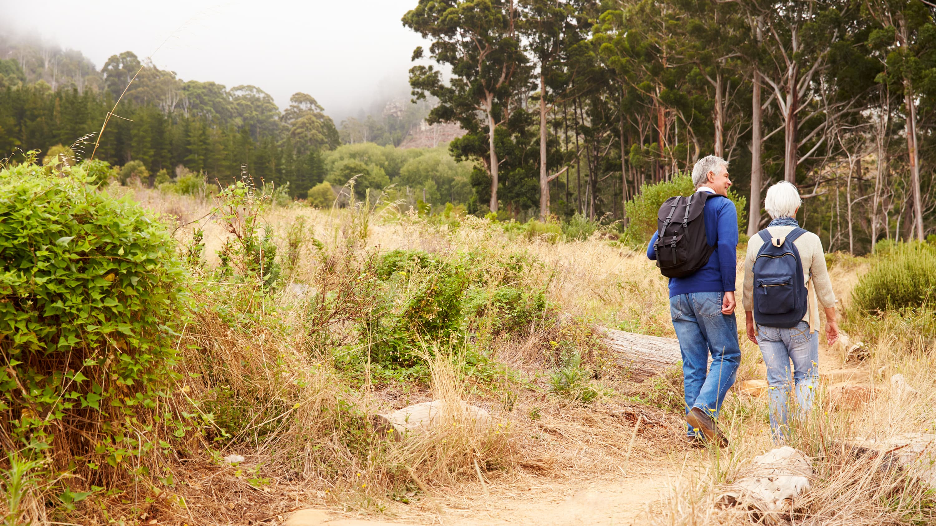 An older couple, one of whom has a spinal deformity, walk on a trail.