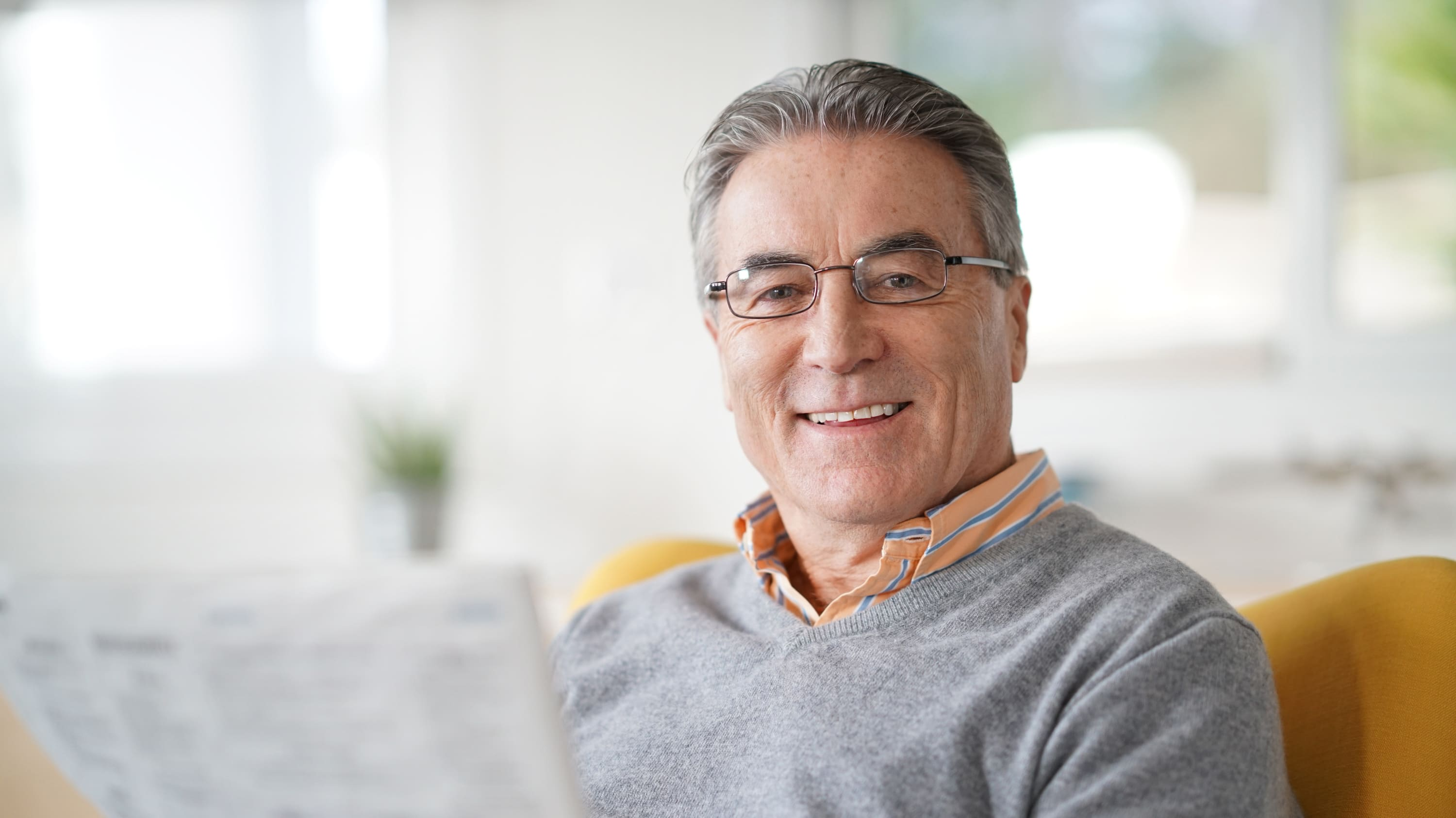A senior man with glasses is relaxing with a newspaper and  may be reading about interventional oncology treatment.