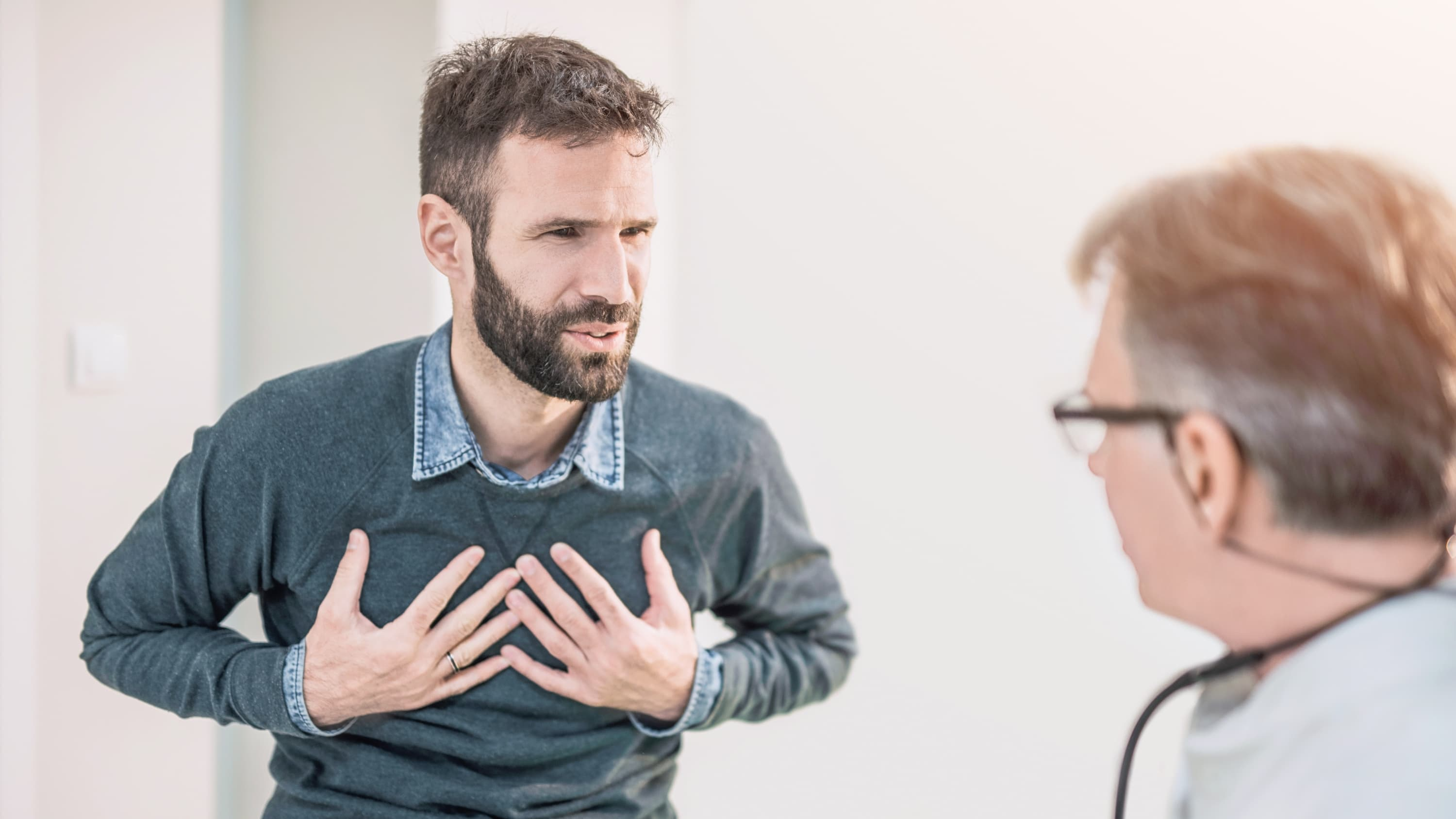 Man describes holds his chest while talking to his doctor about a possible adult congenital heart problem.