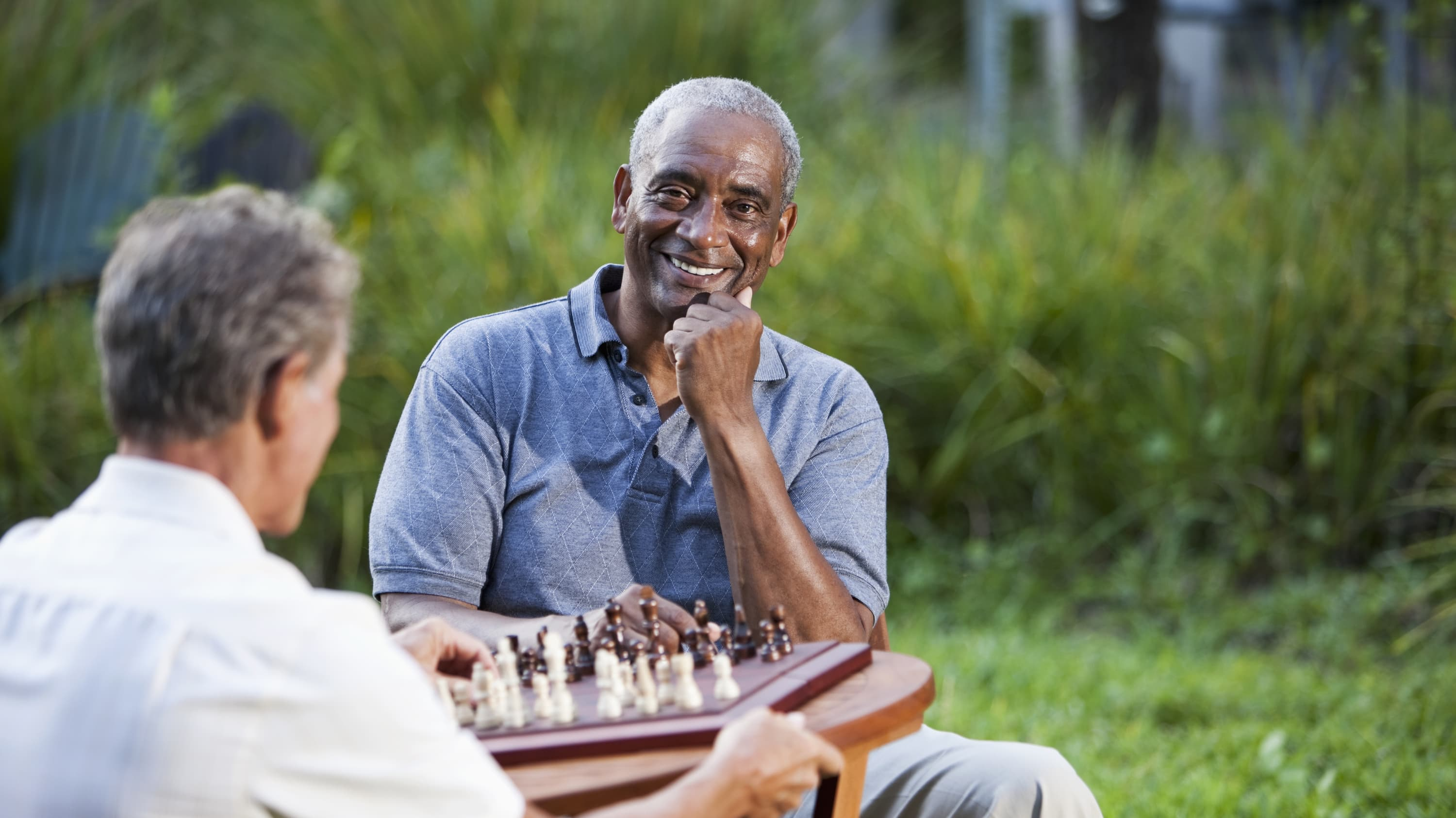 A senior African American man who may need a UroLift plays chess.