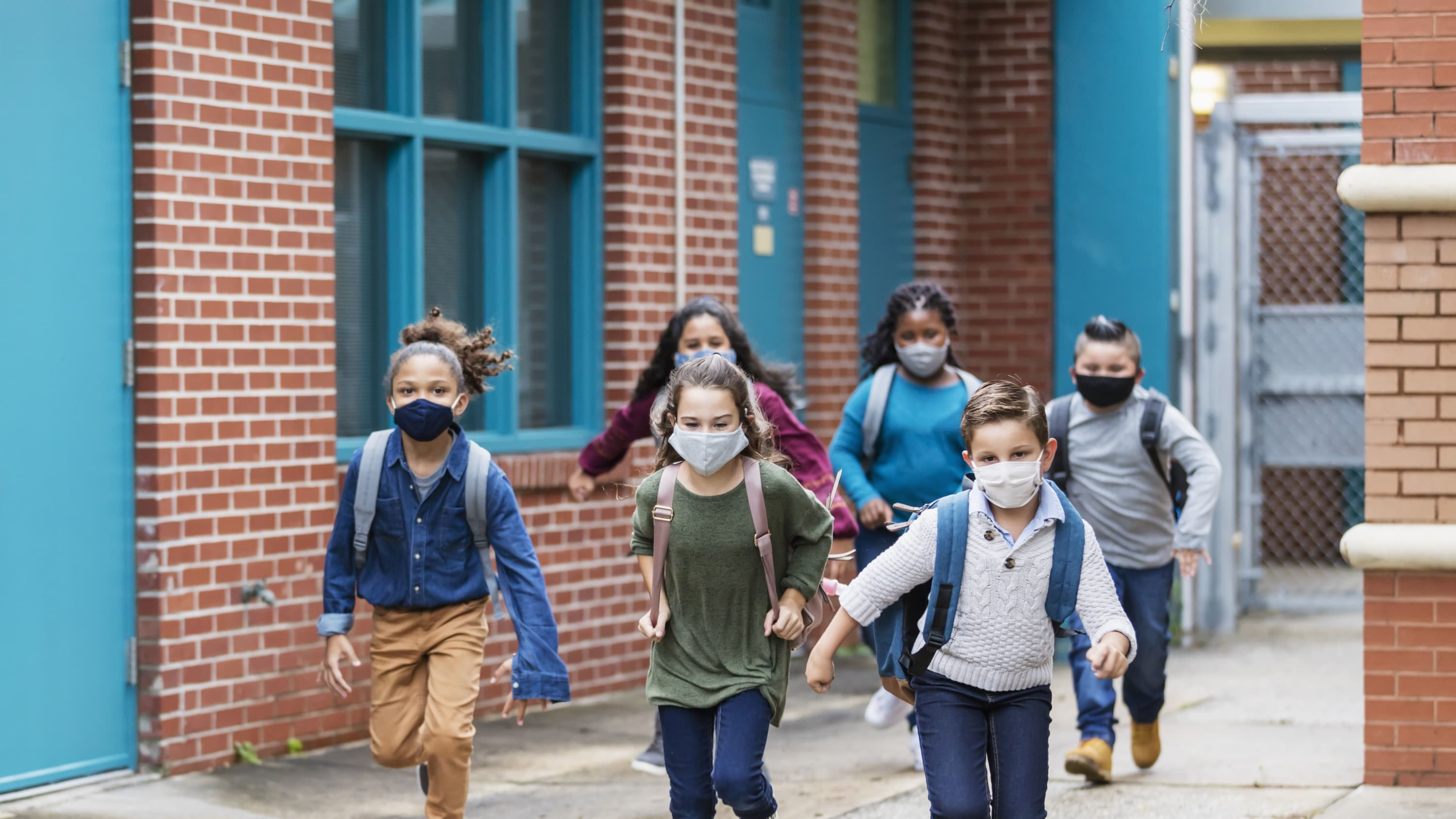 children running outside of school, after COVID-19 vaccination
