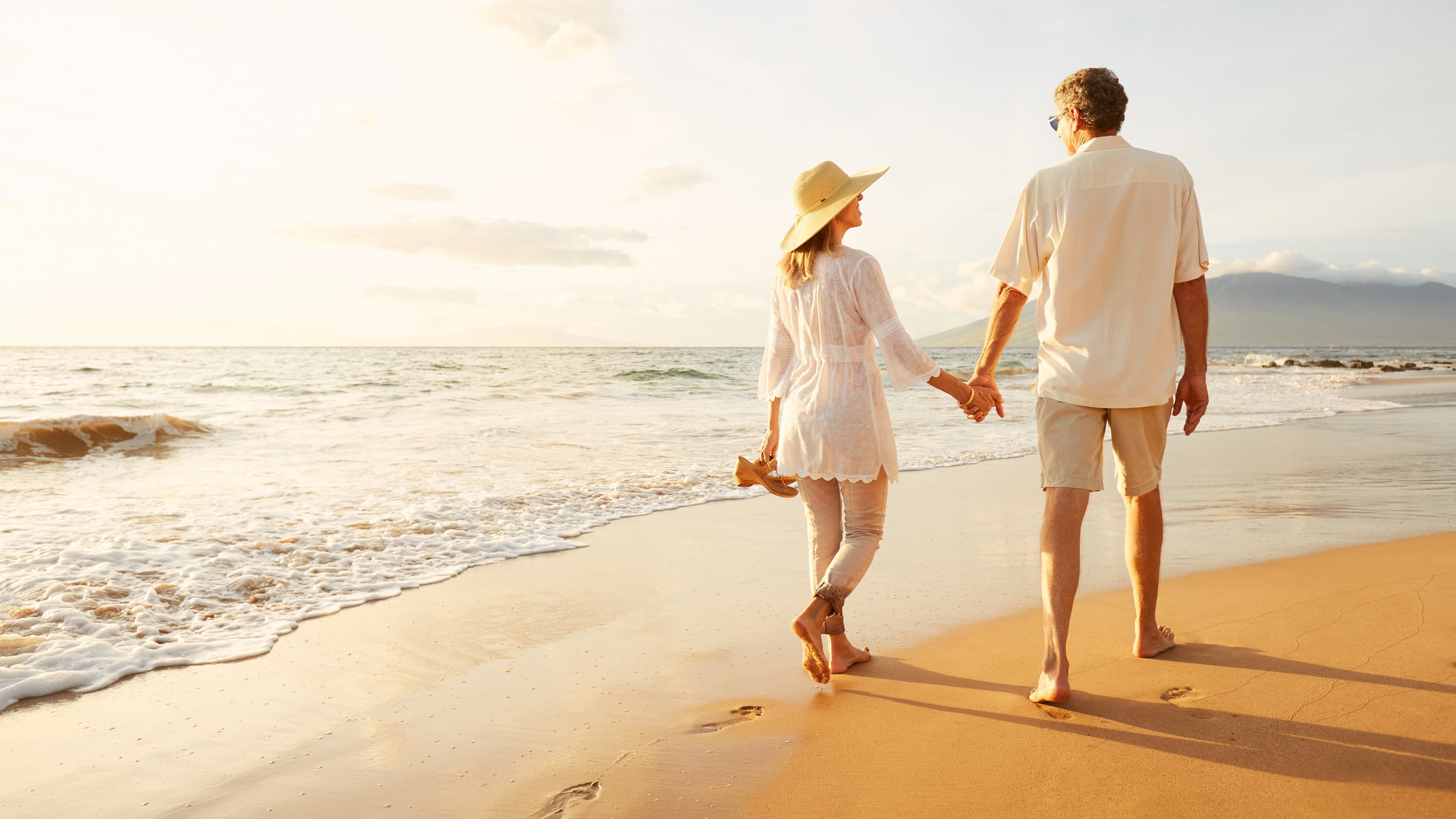 A couple strolls on the beach.after the man has had a vasectomy reversal.