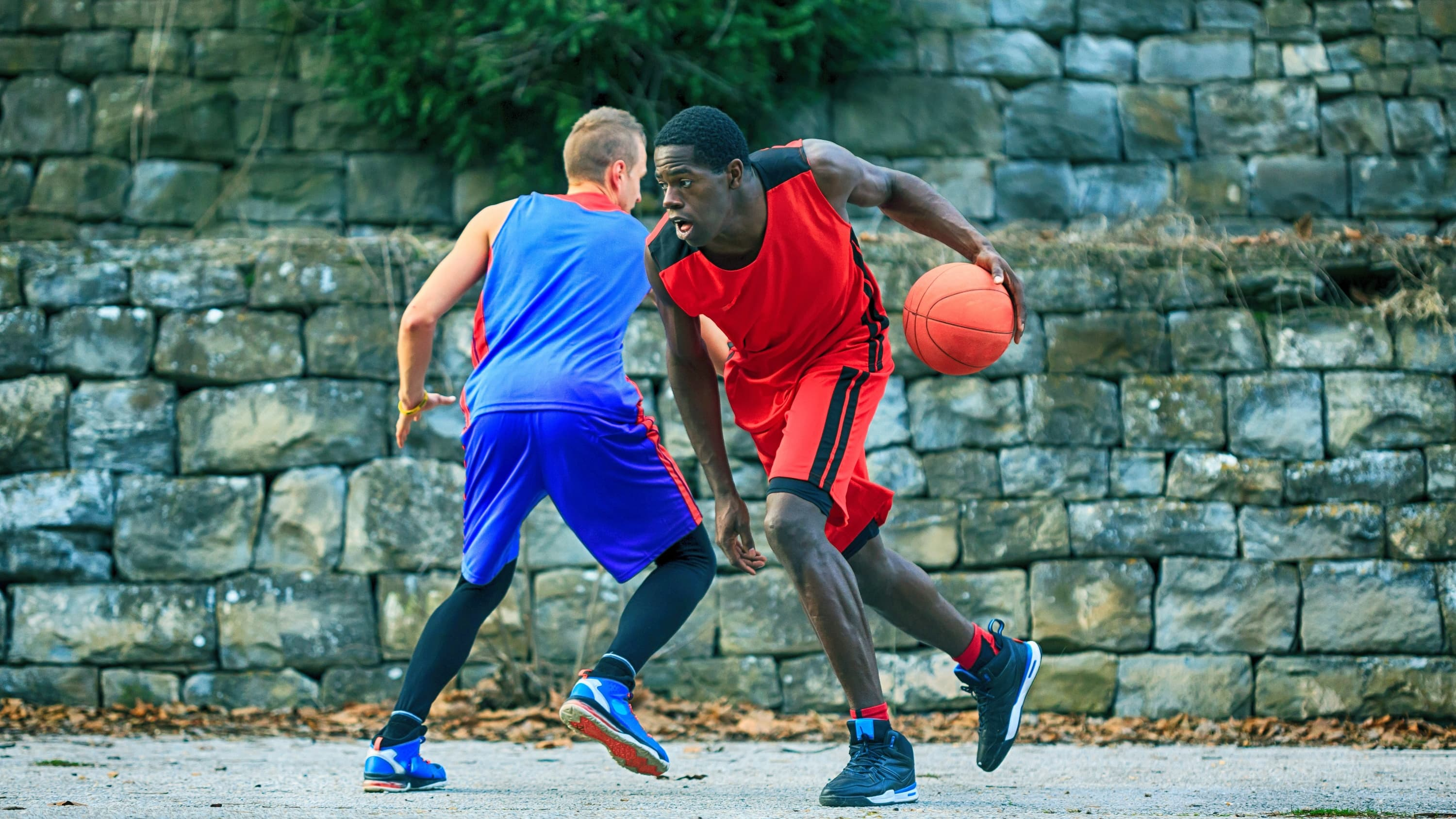 Two young people play basketball in a park.