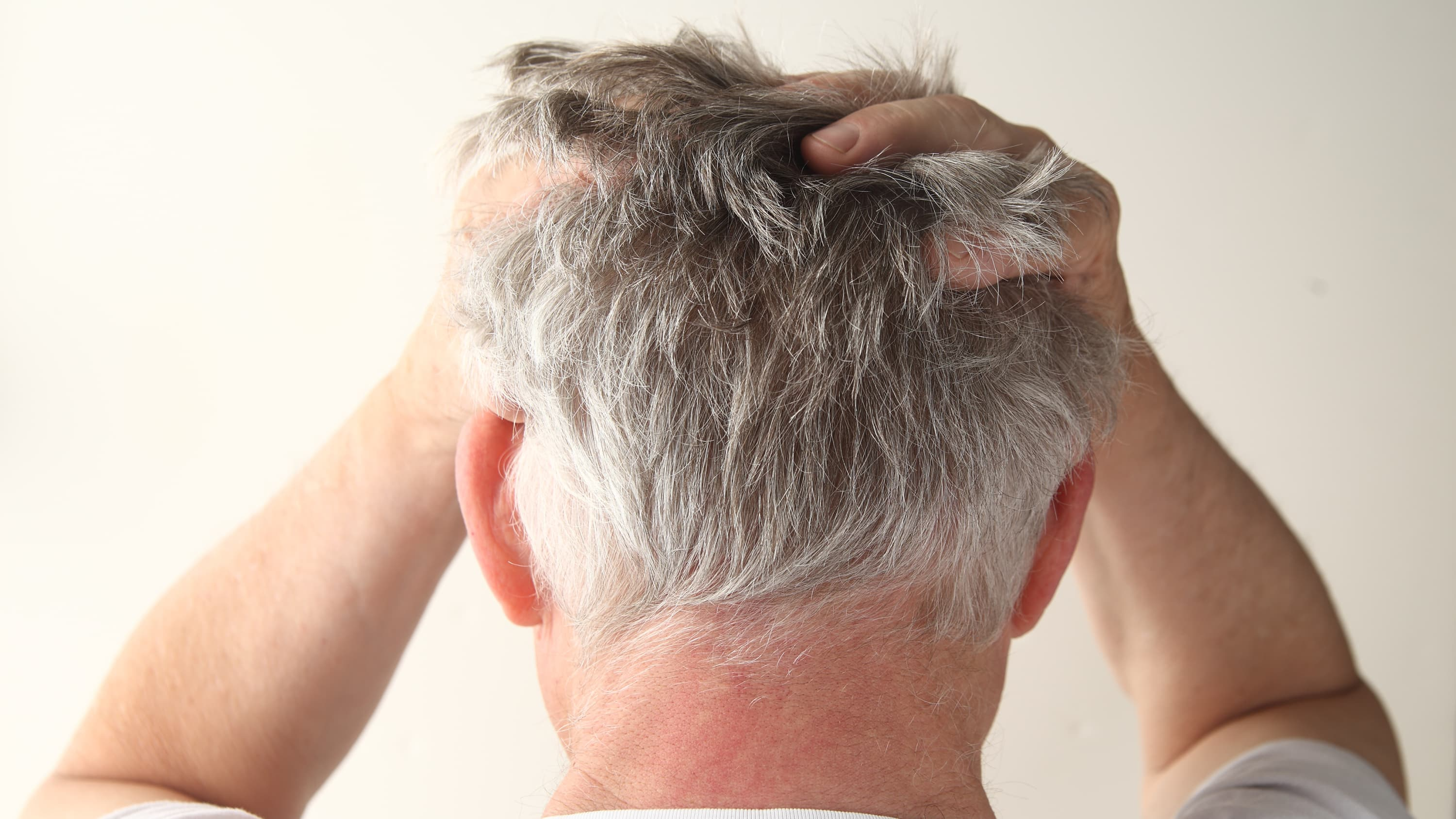 A man with a primary brain tumor holds his head.