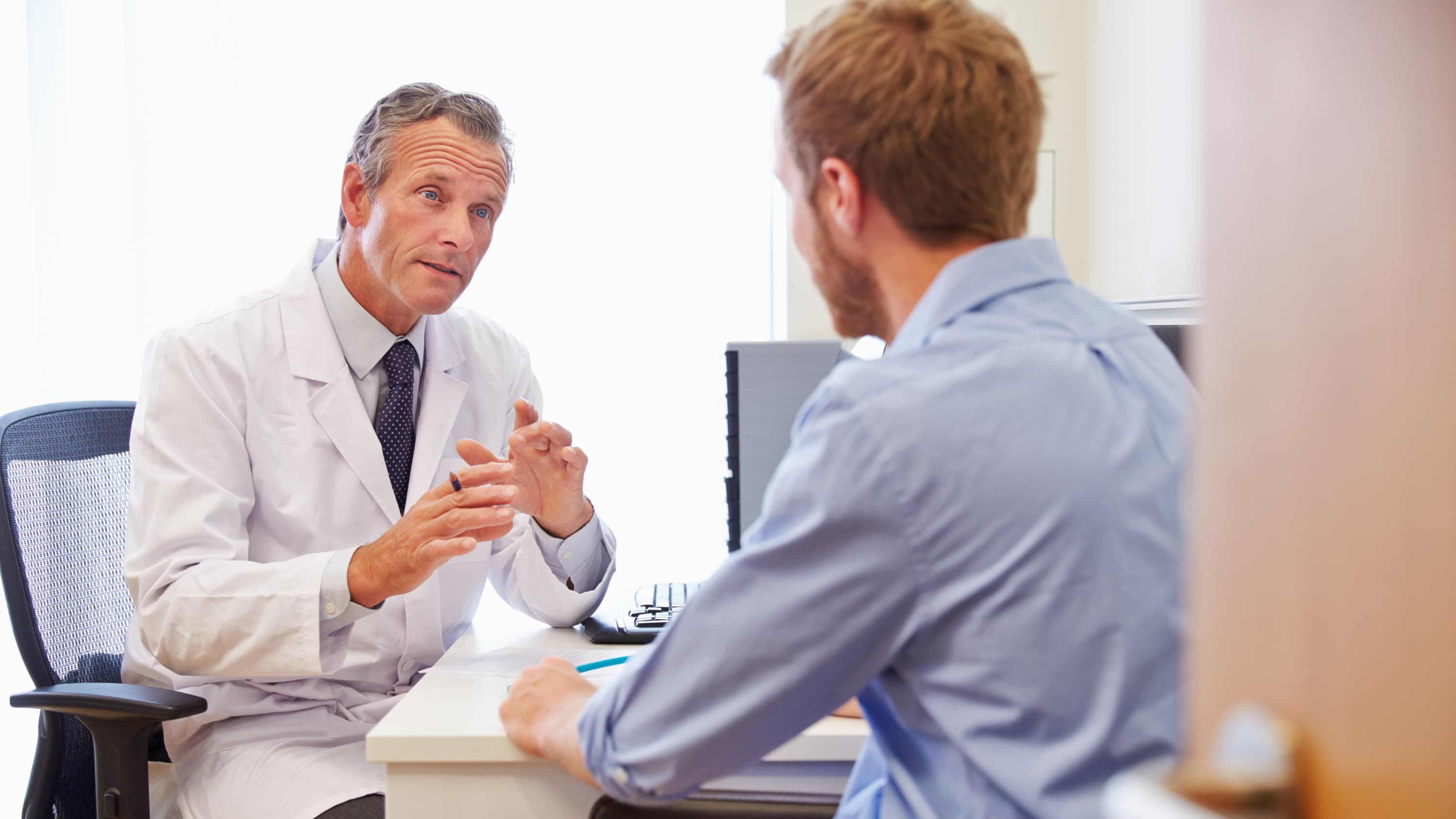 A doctor consults with his male patient who is in the age group that testicular cancer affects--15- to 34-year-olds.