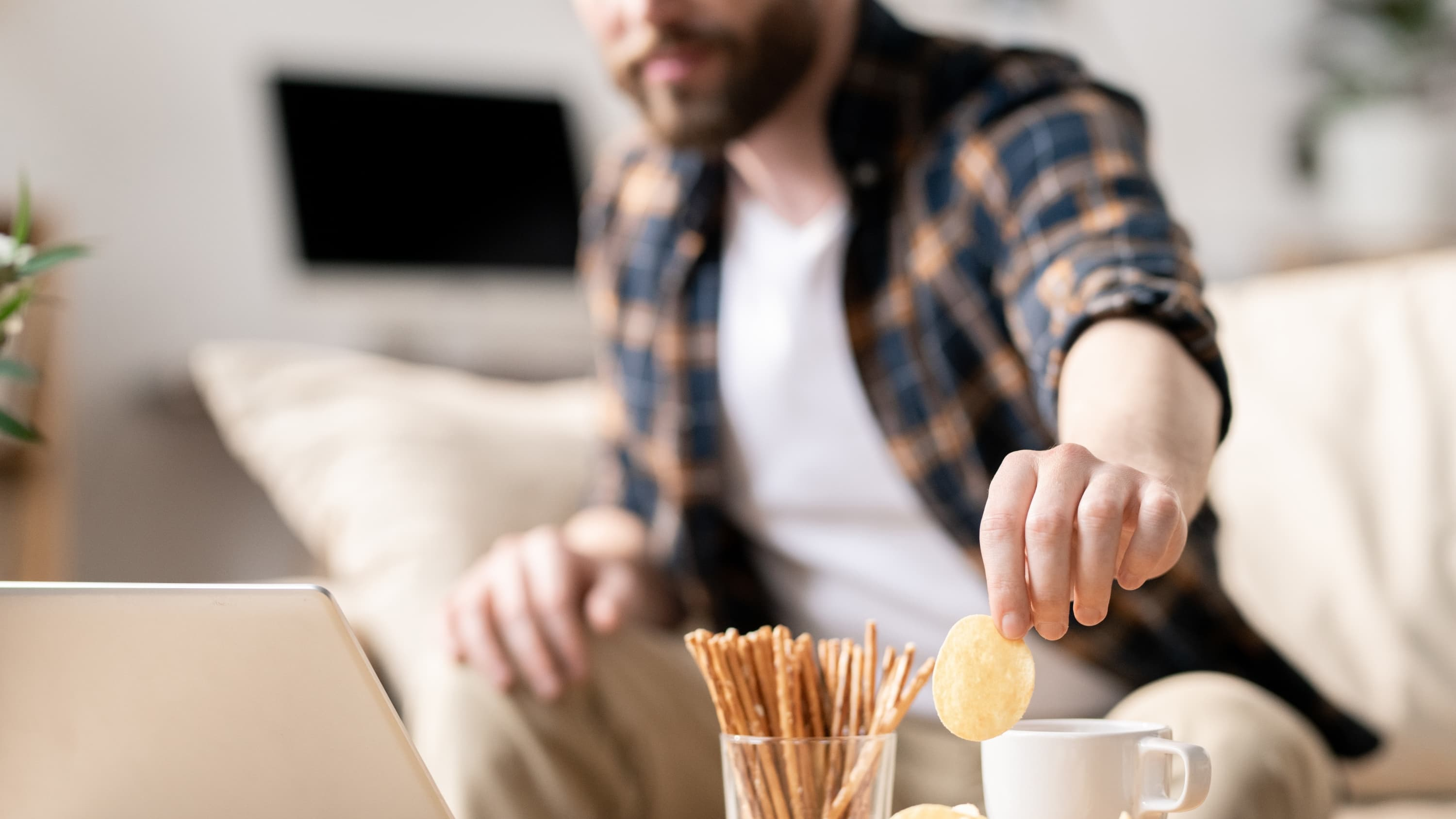 Man snacking, possibly in response to anxiety related to the COVID-19 pandemic