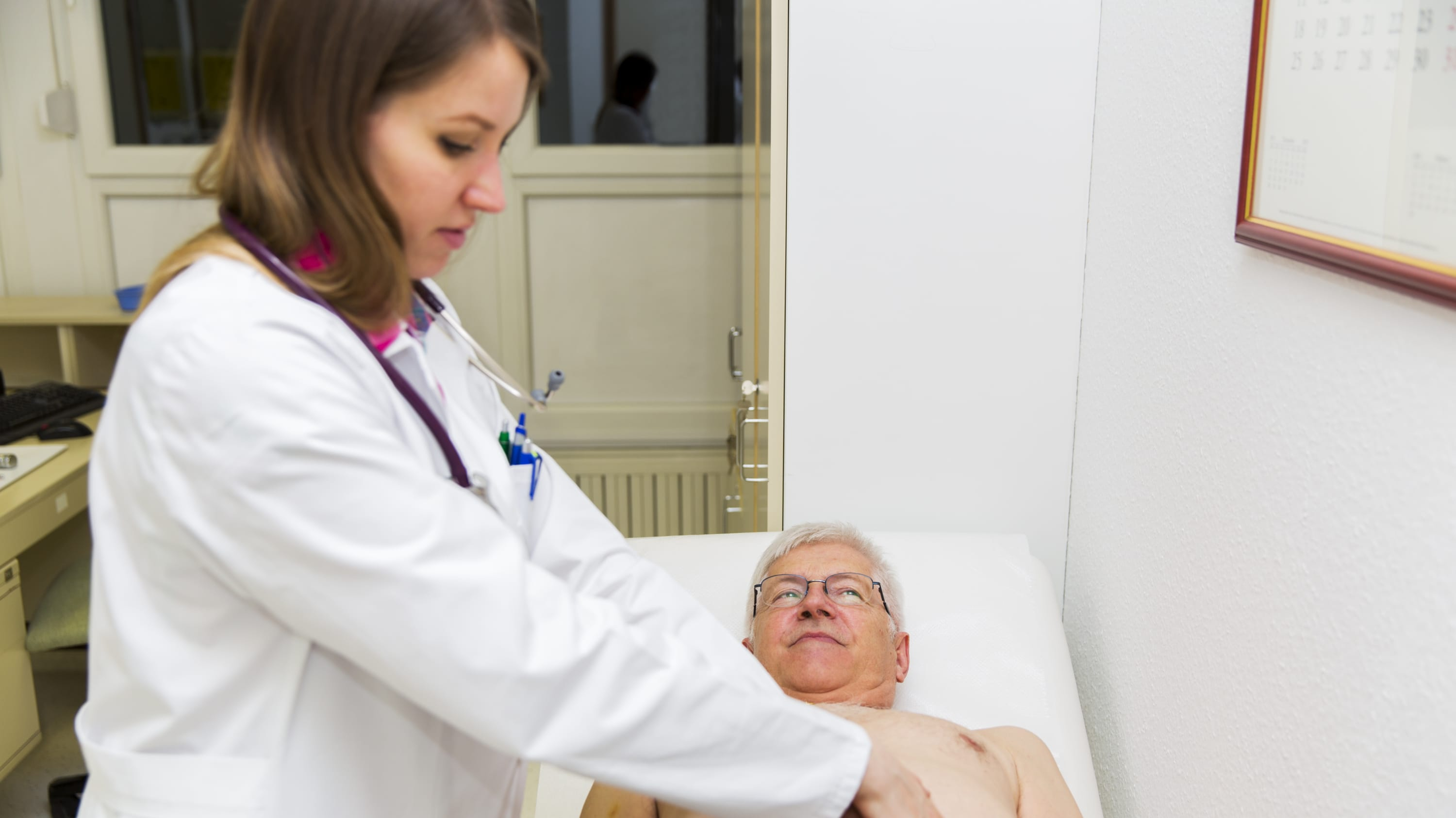 A doctor examines an older man who may be a candidate for a liver transplant.