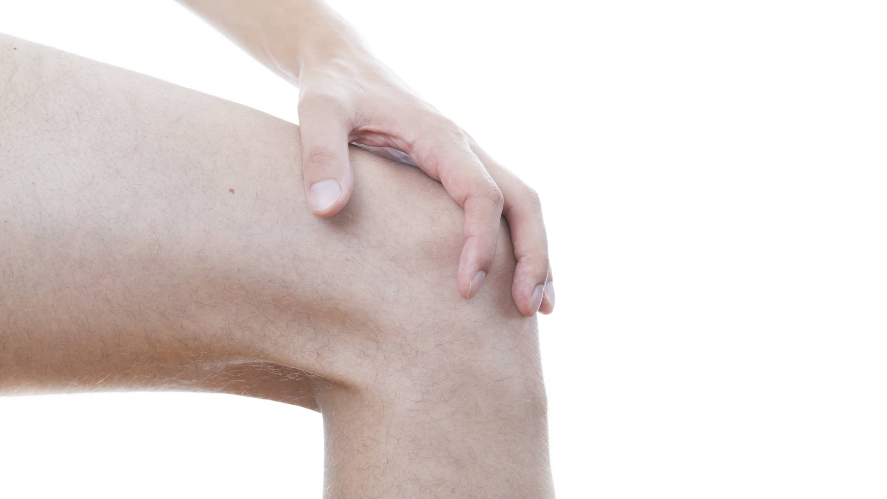 A hand itches the top of a bare knee, possibly because of eczema
