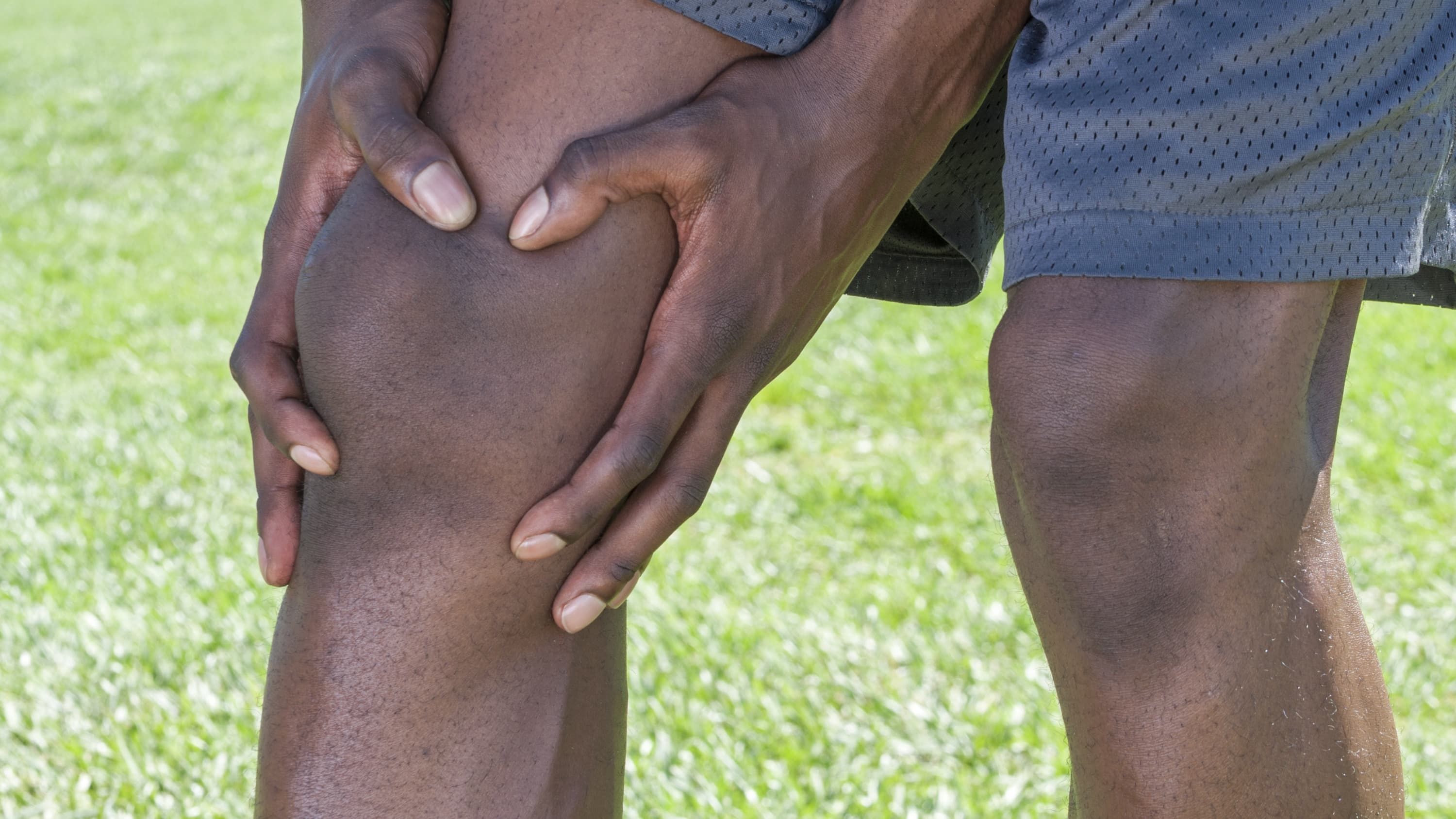 A man holds his knee, he may be developing osteoarthritis.