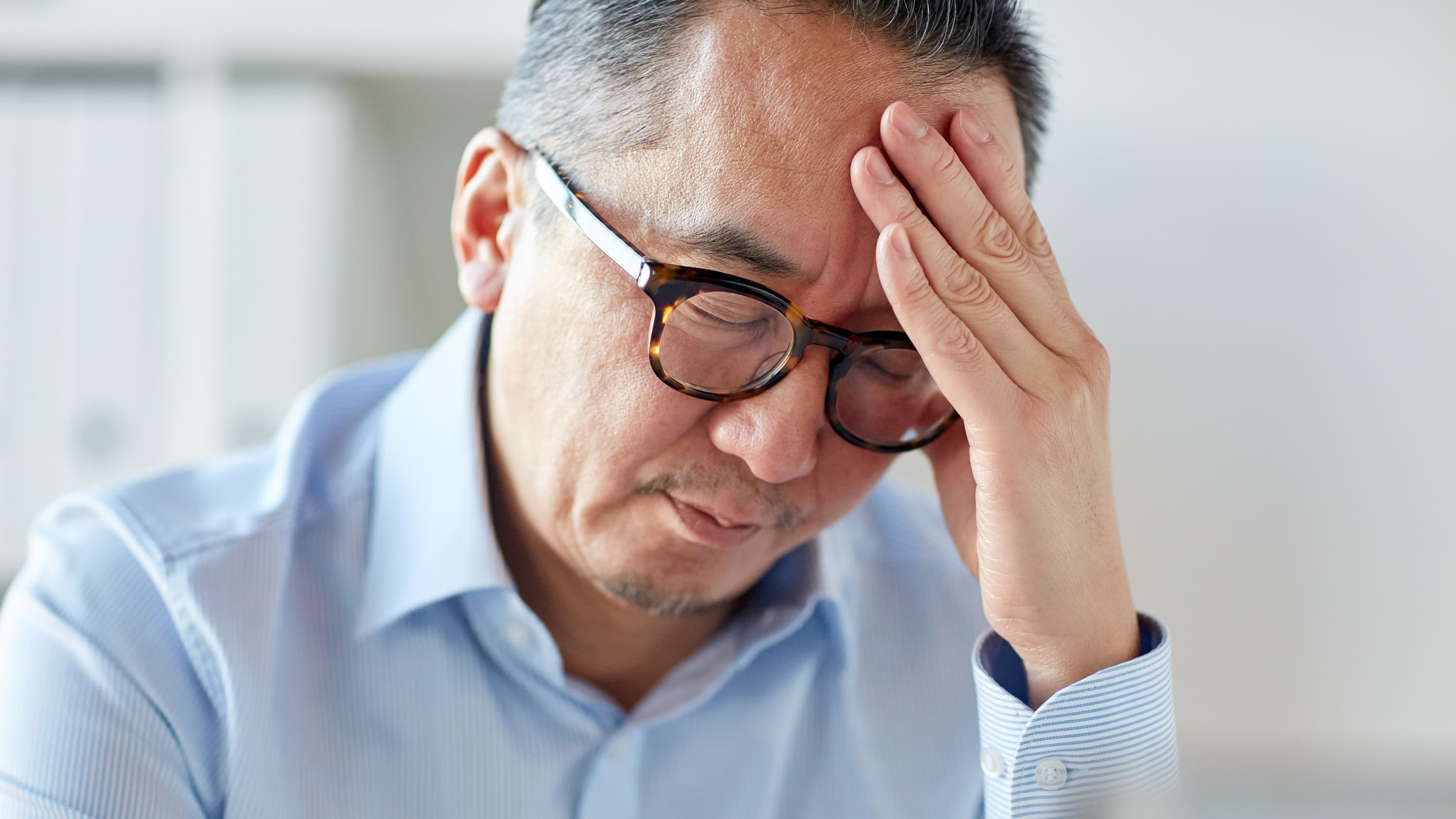 close up of tired businessman in eyeglasses suffering from headache at office