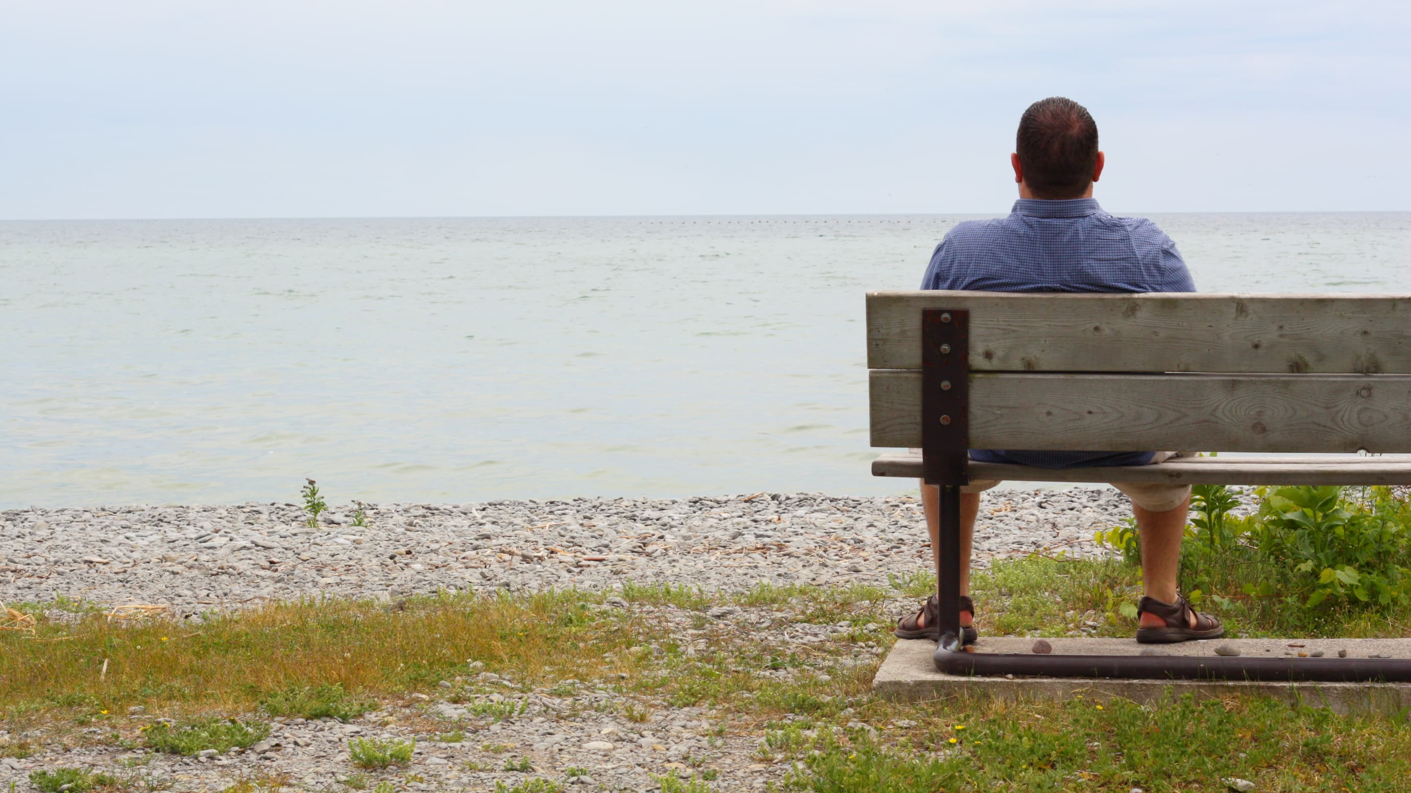 A man coping with heart failure sits on a bench at the beach looking out at the water.