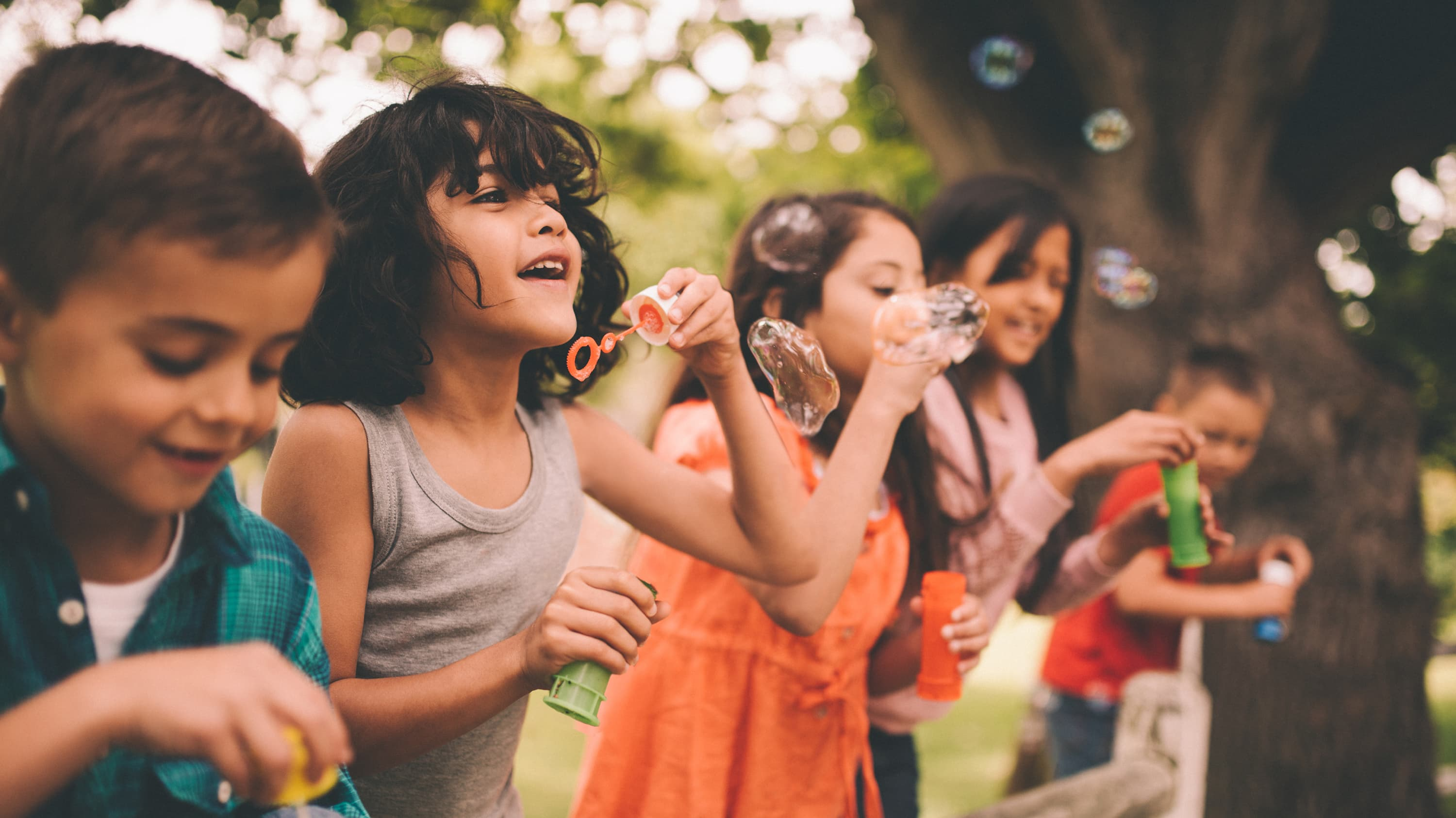 A child recovered from a brain tumor plays outside with friends.