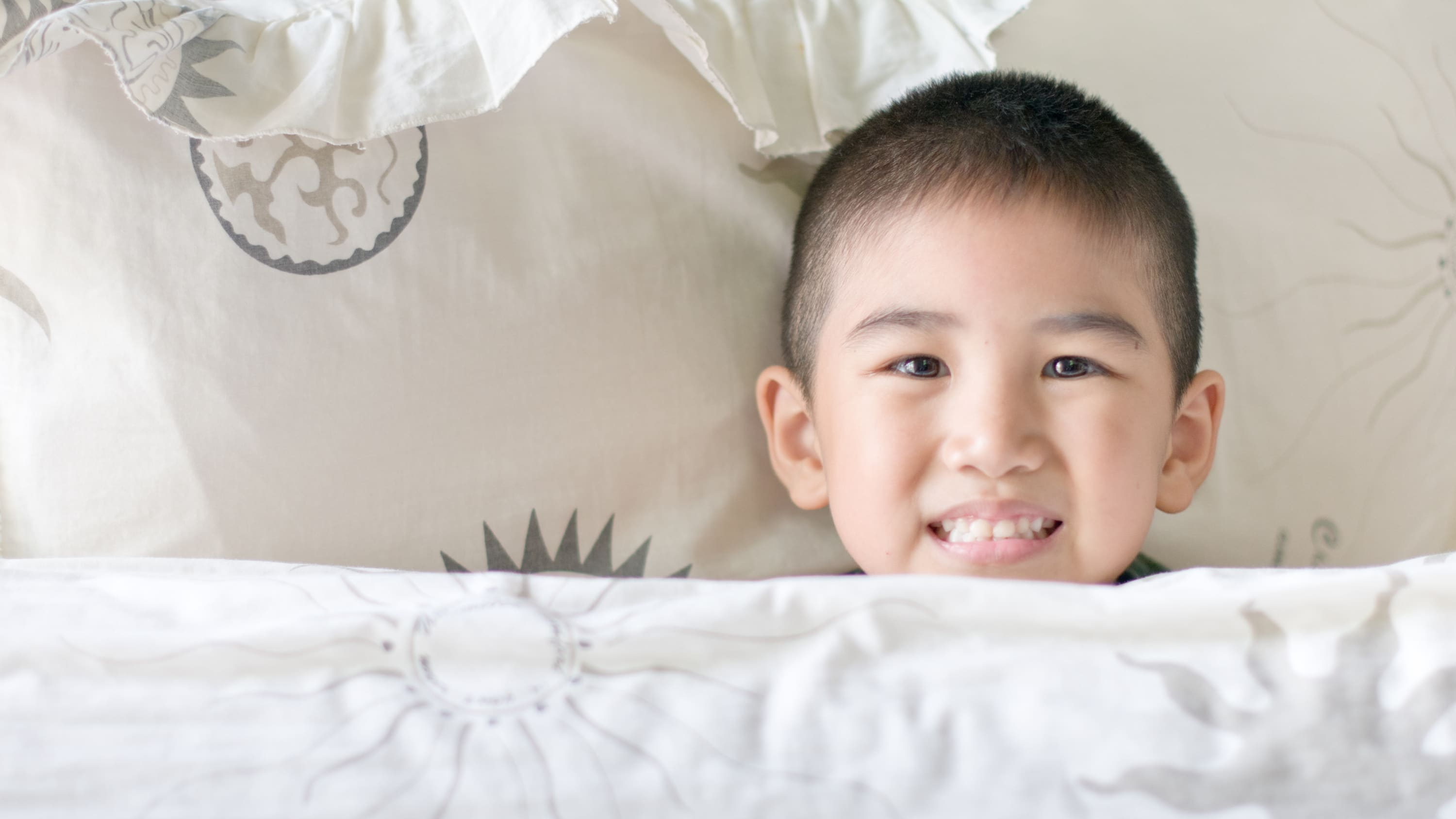 A boy rests in bed. He may need a sleep study to figure out why he has problems sleeping.