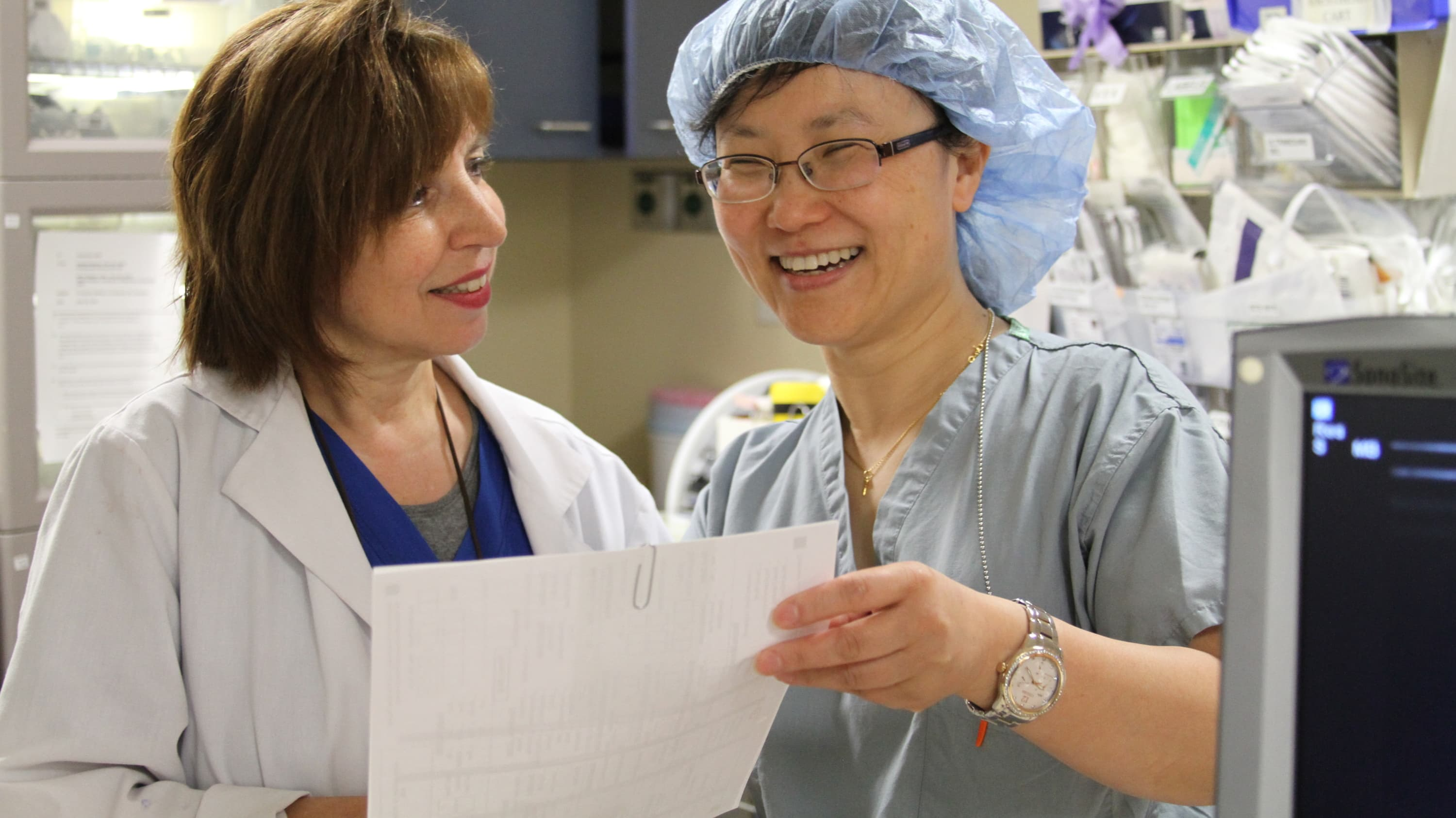 Nerve block nurse Lisa Mastrangello (on the left) with Jinlei Li, MD, an anesthesiologist, discussing a nerve block, which is a type of regional anesthesia.