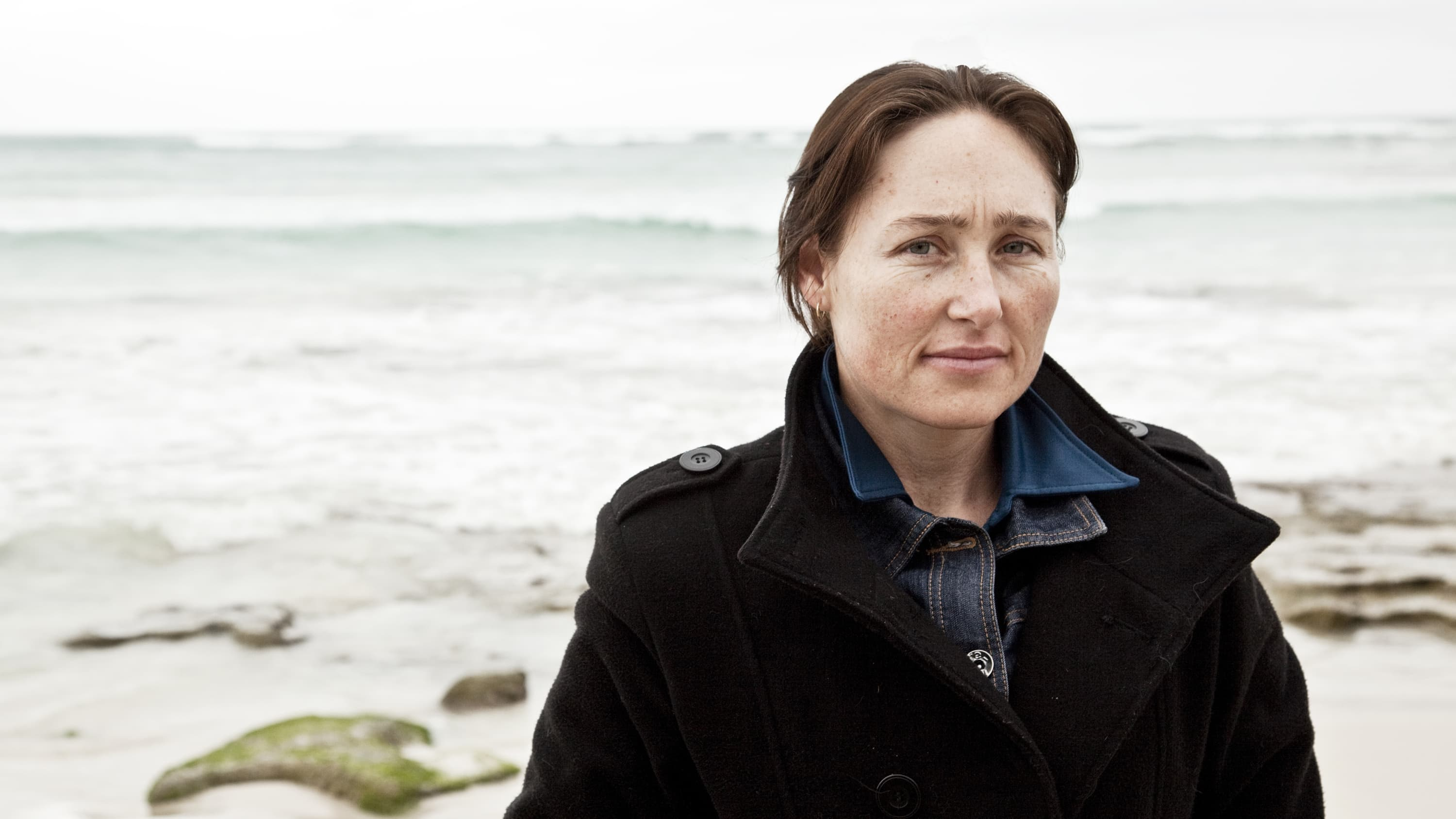 A woman on the beach looking worried, possibly because of a breast cancer diagnosis.