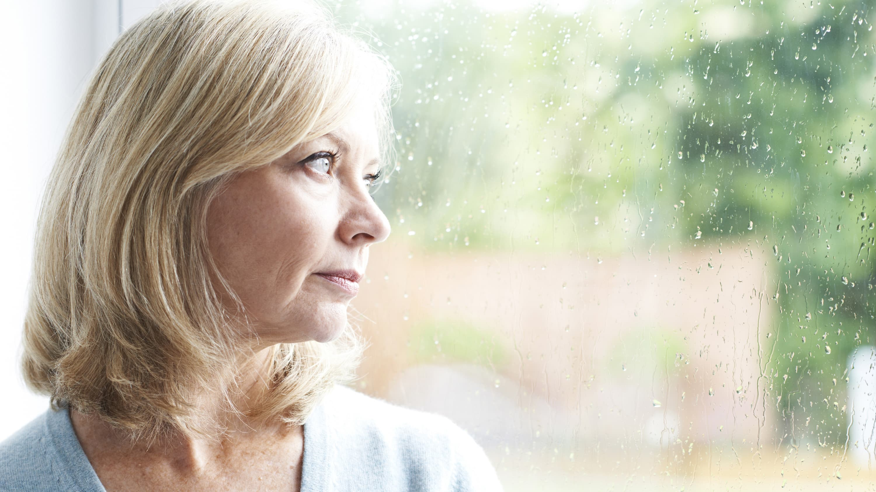 Mature woman who has Wilson disease gazing out a window.