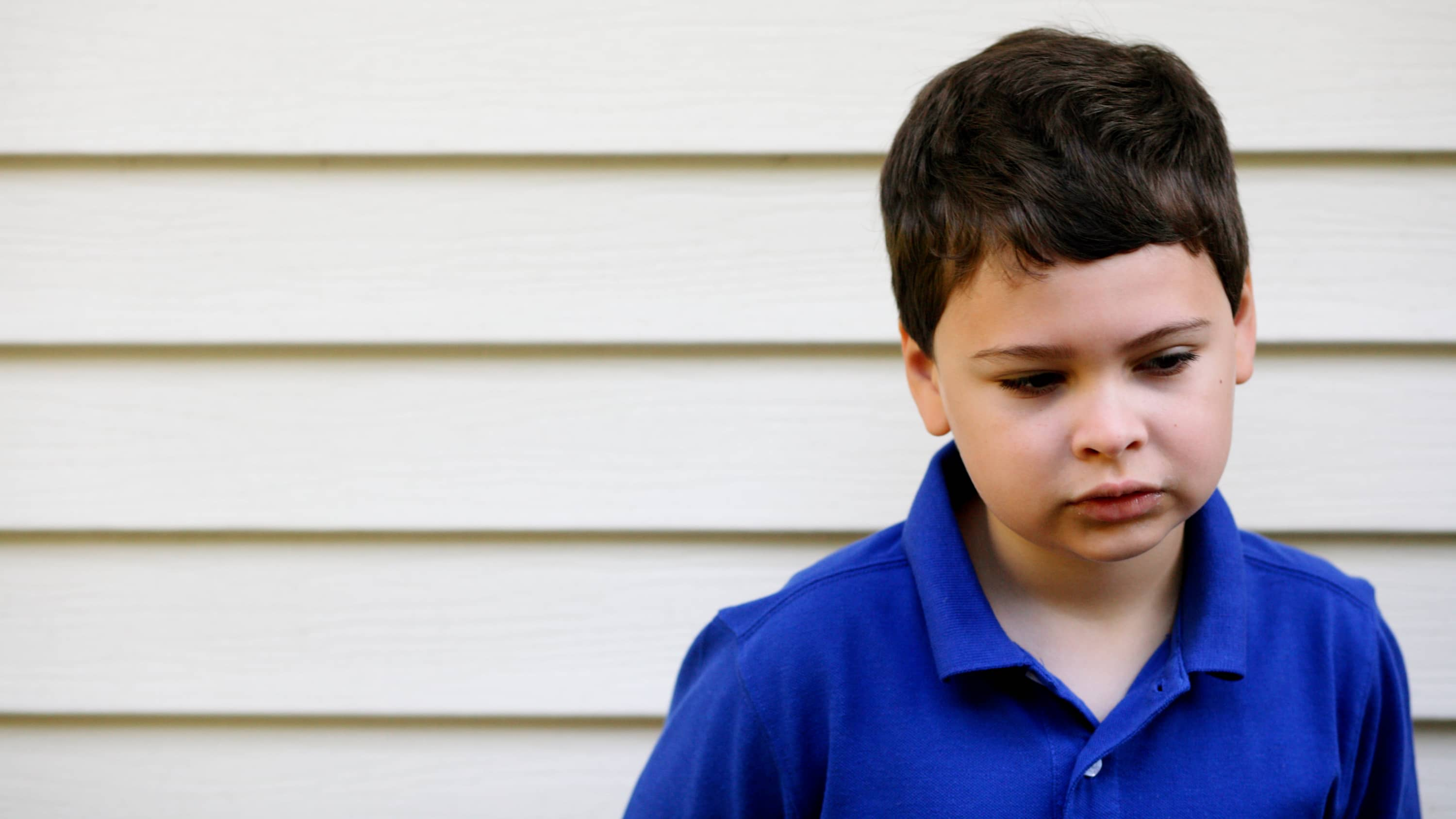 A young boy in a blue shirt who may have autism stands outside with a serious look on his face.