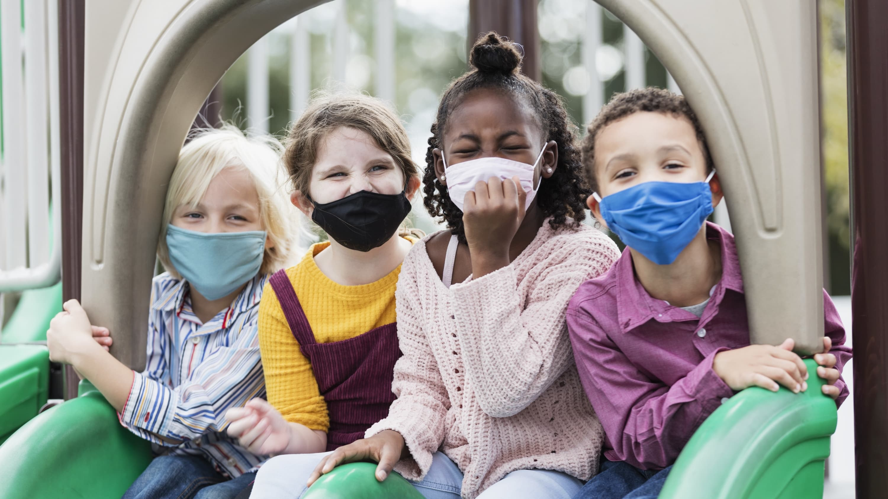 masked kids in a playground who might benefit from COVID-19 vaccine clinical trials