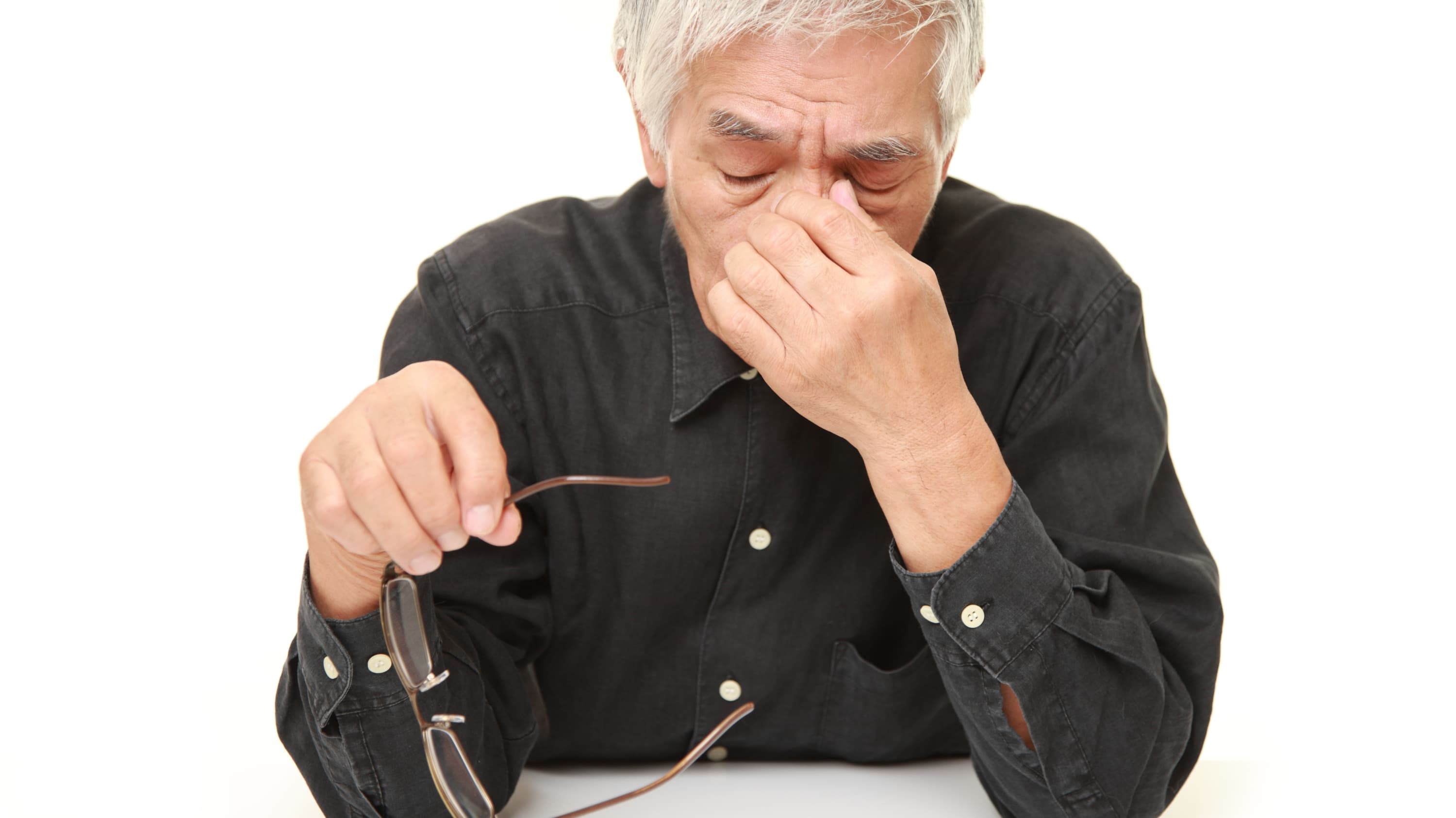 A man rubs his eyes, possibly because he has dry eyes.