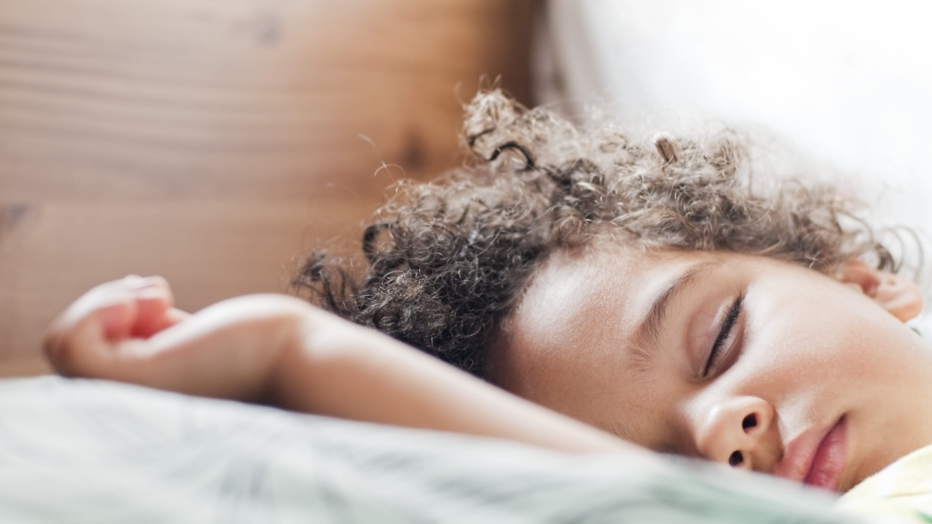 A little girl who may have obstruction sleep apnea is fast asleep in bed.