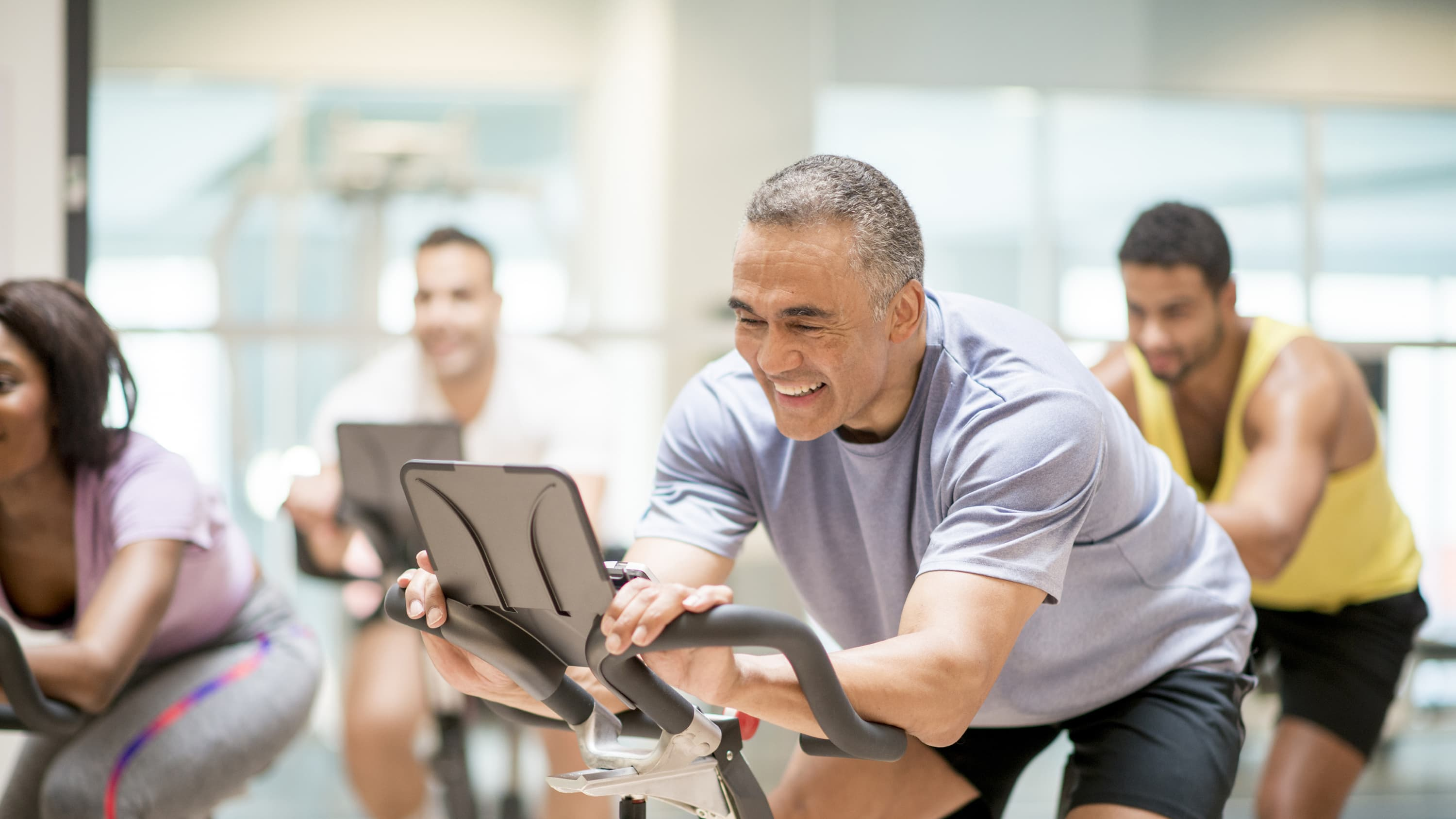 A middle-aged man is back in the gym on the exercise bike after treatment for coronary atherosclerosis.