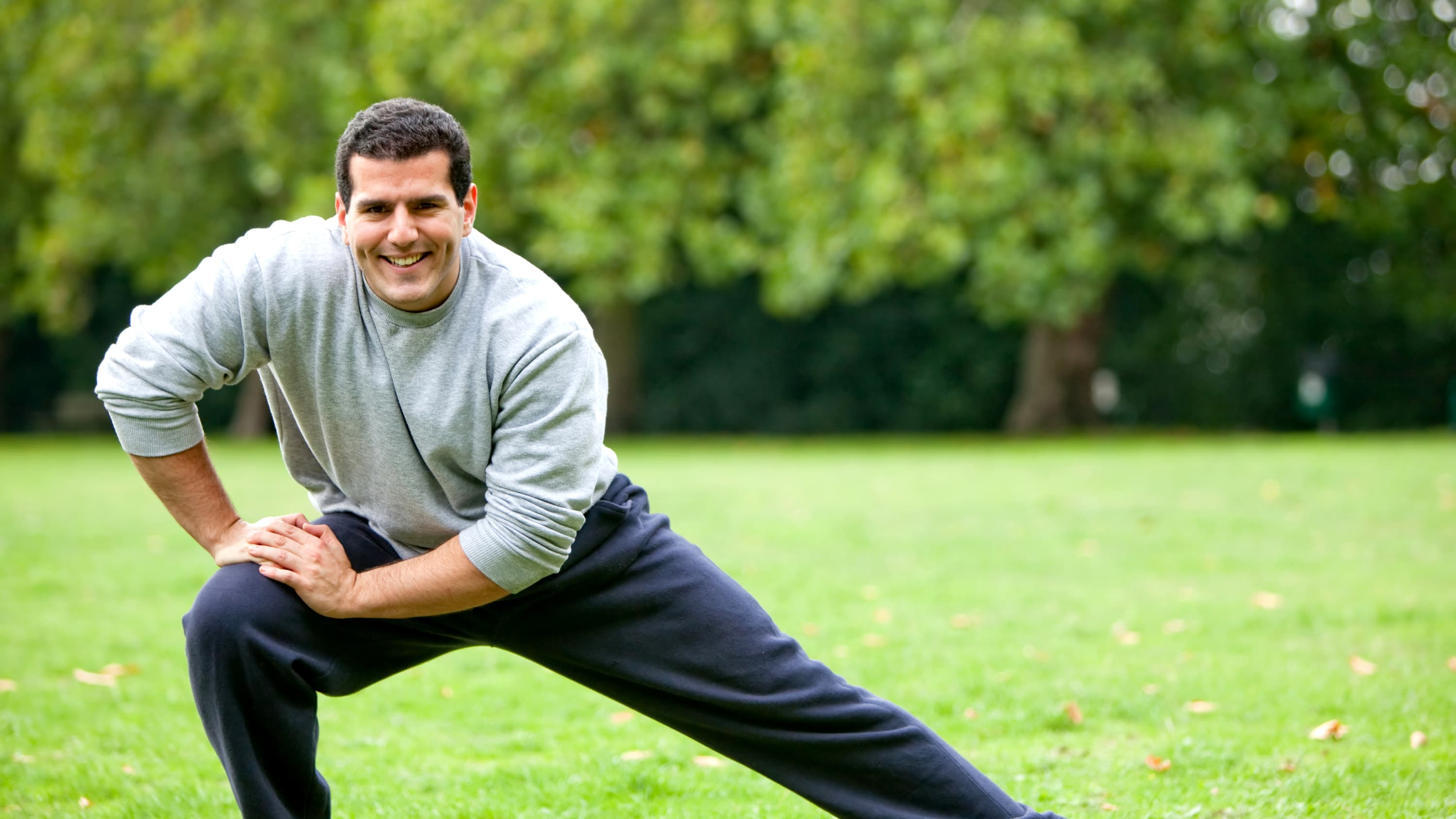 An athletic man in sweatpants who finally has pain relief after surgery stretches in the park.