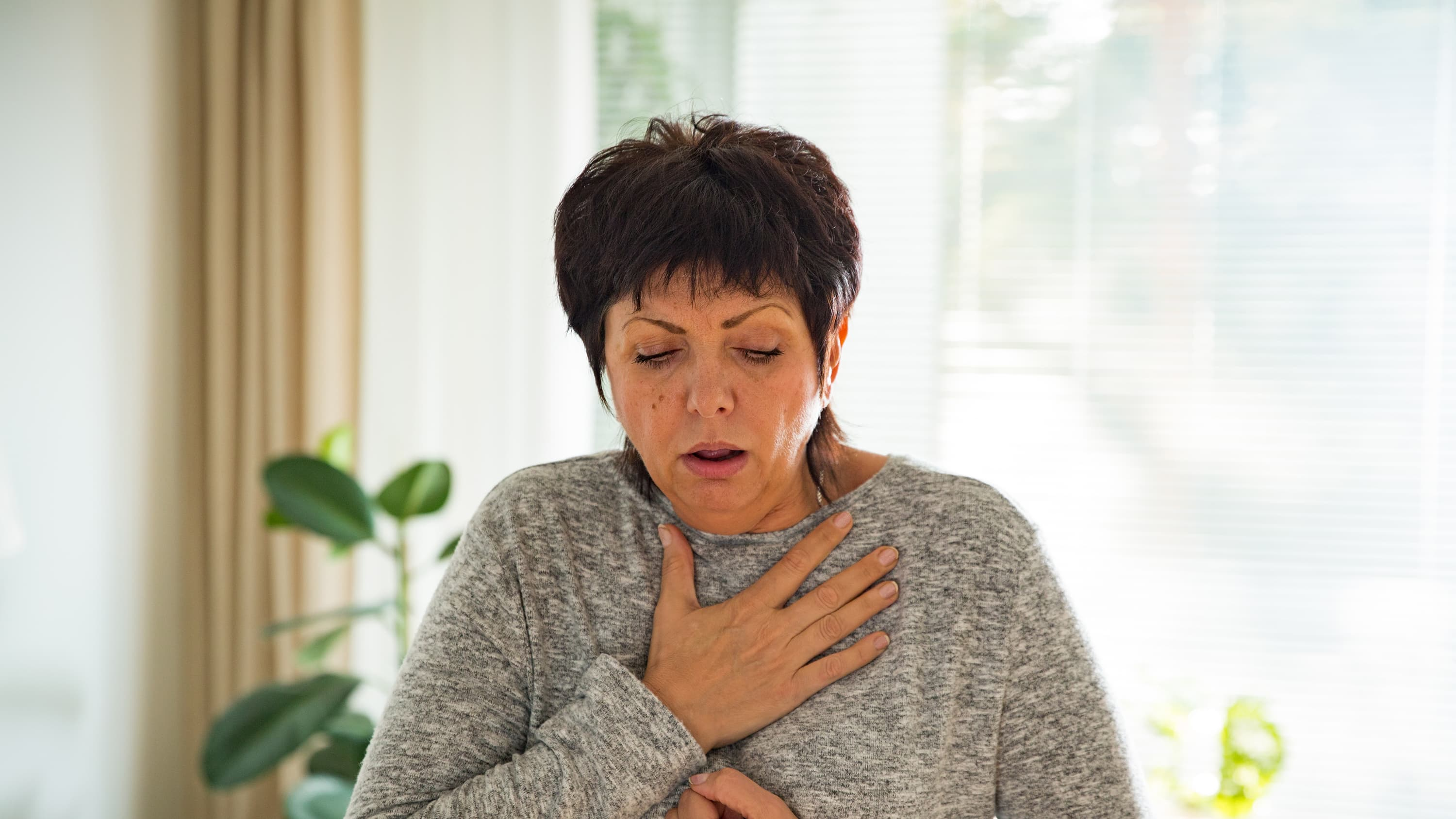 A woman suffering with dypnea struggling to breath.