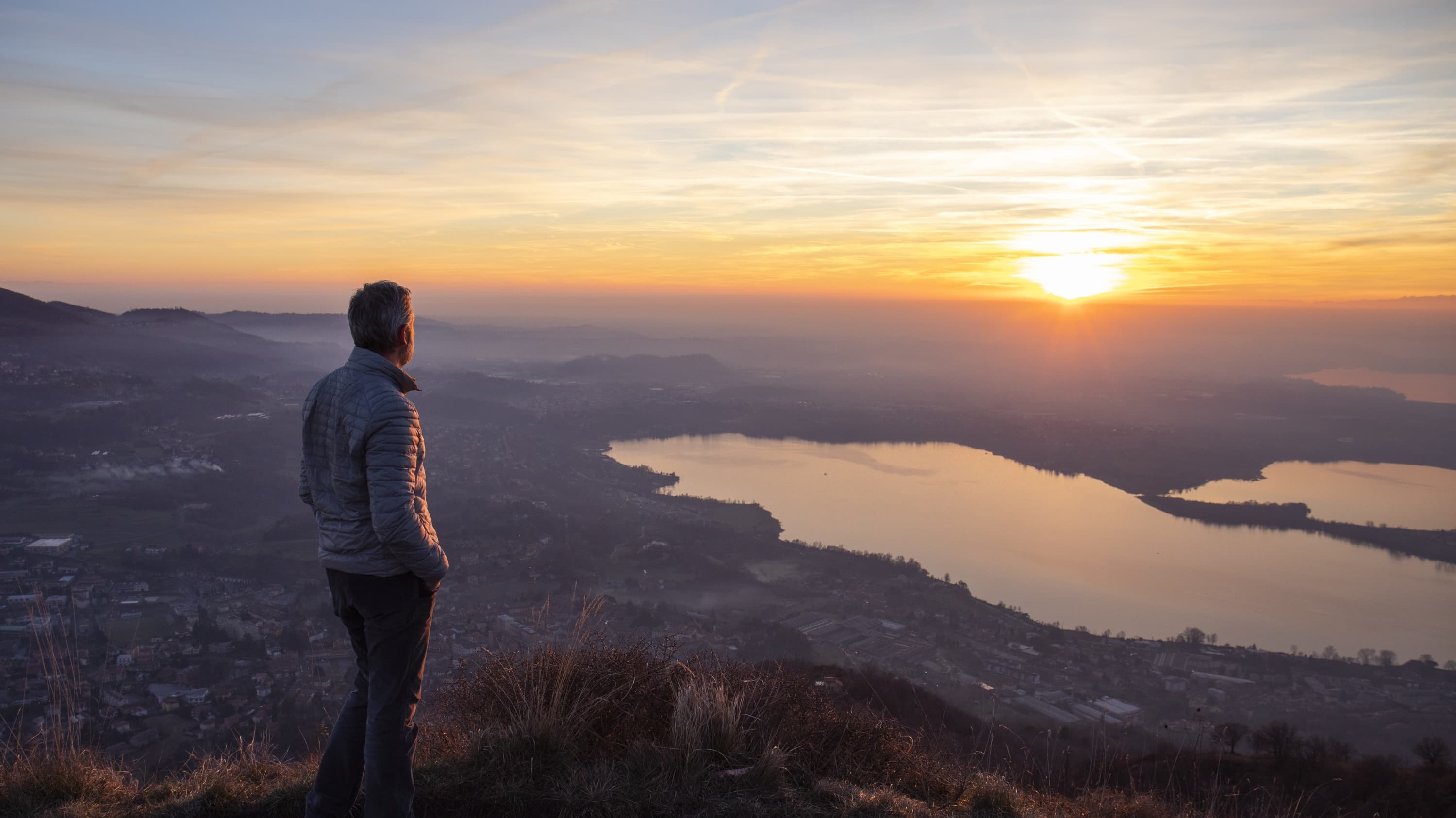 Hiker looking sun over horizon, possibly worried about neoplasm