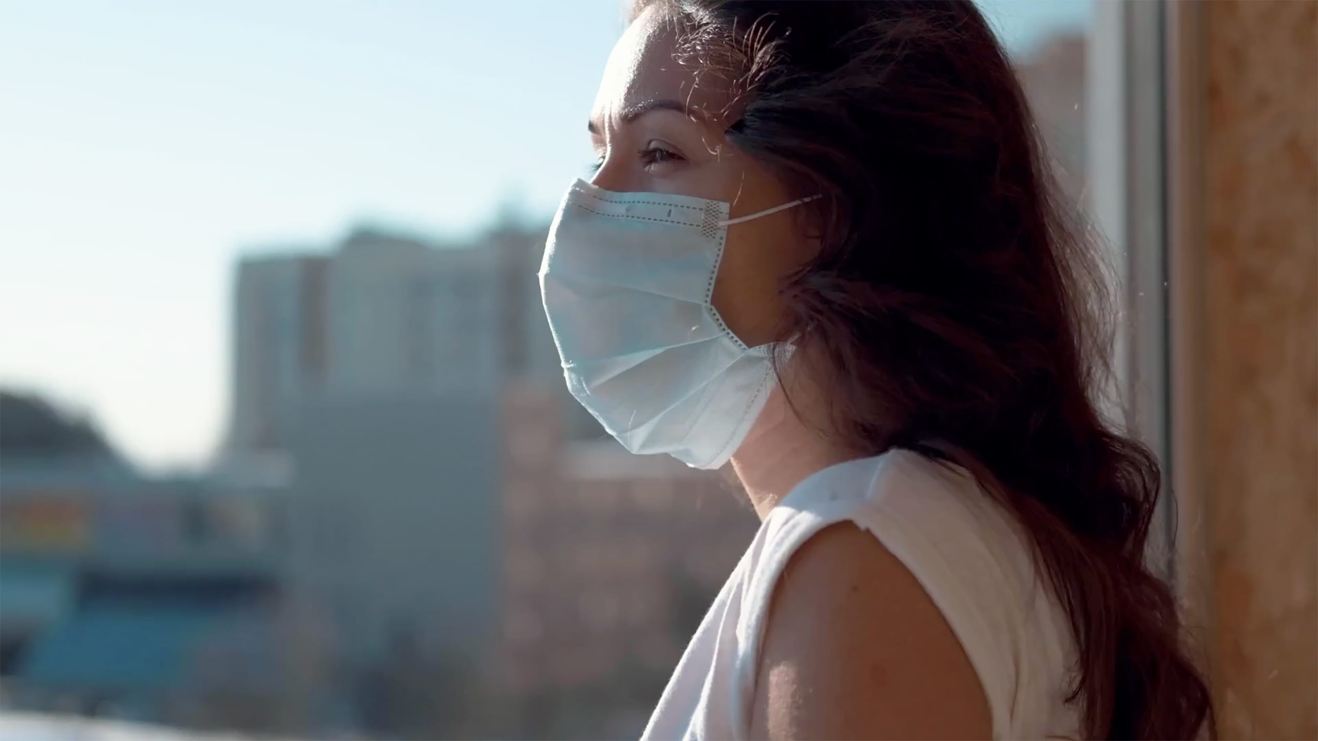 A woman wears a mask alone in her apartment during the COVID-19 pandemic.