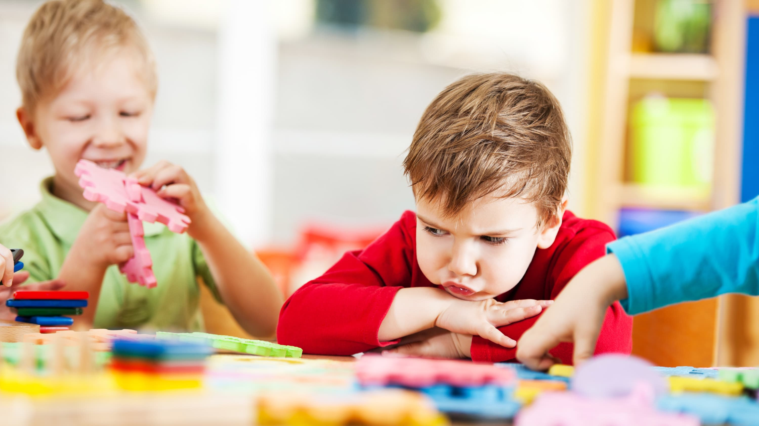 One small boy sulks while another plays in a setting where autism is treated with pivotal response syndrome.
