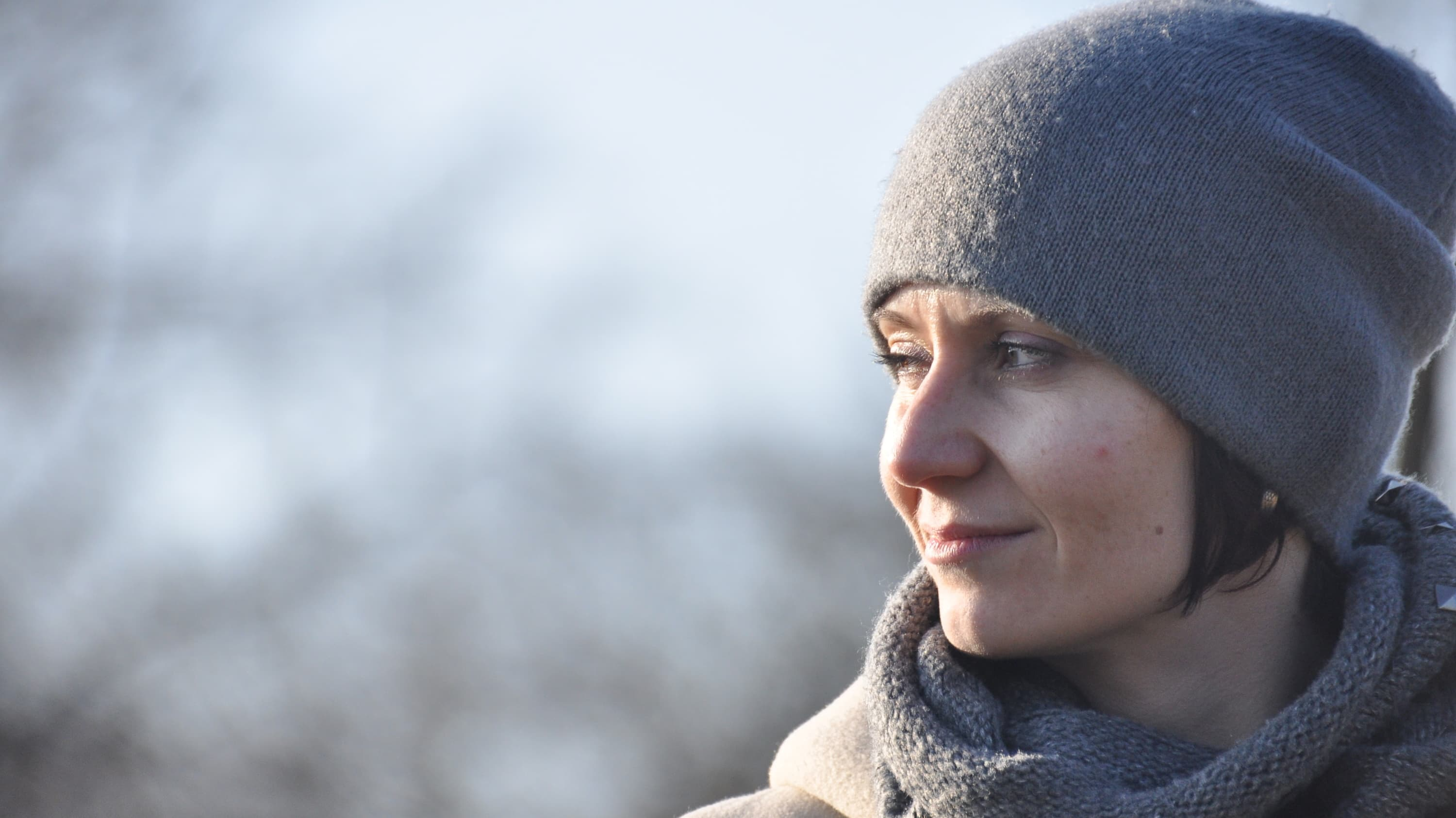 Close up of a woman in a cap and scarf who has had surgery of the upper aero-digestive tract