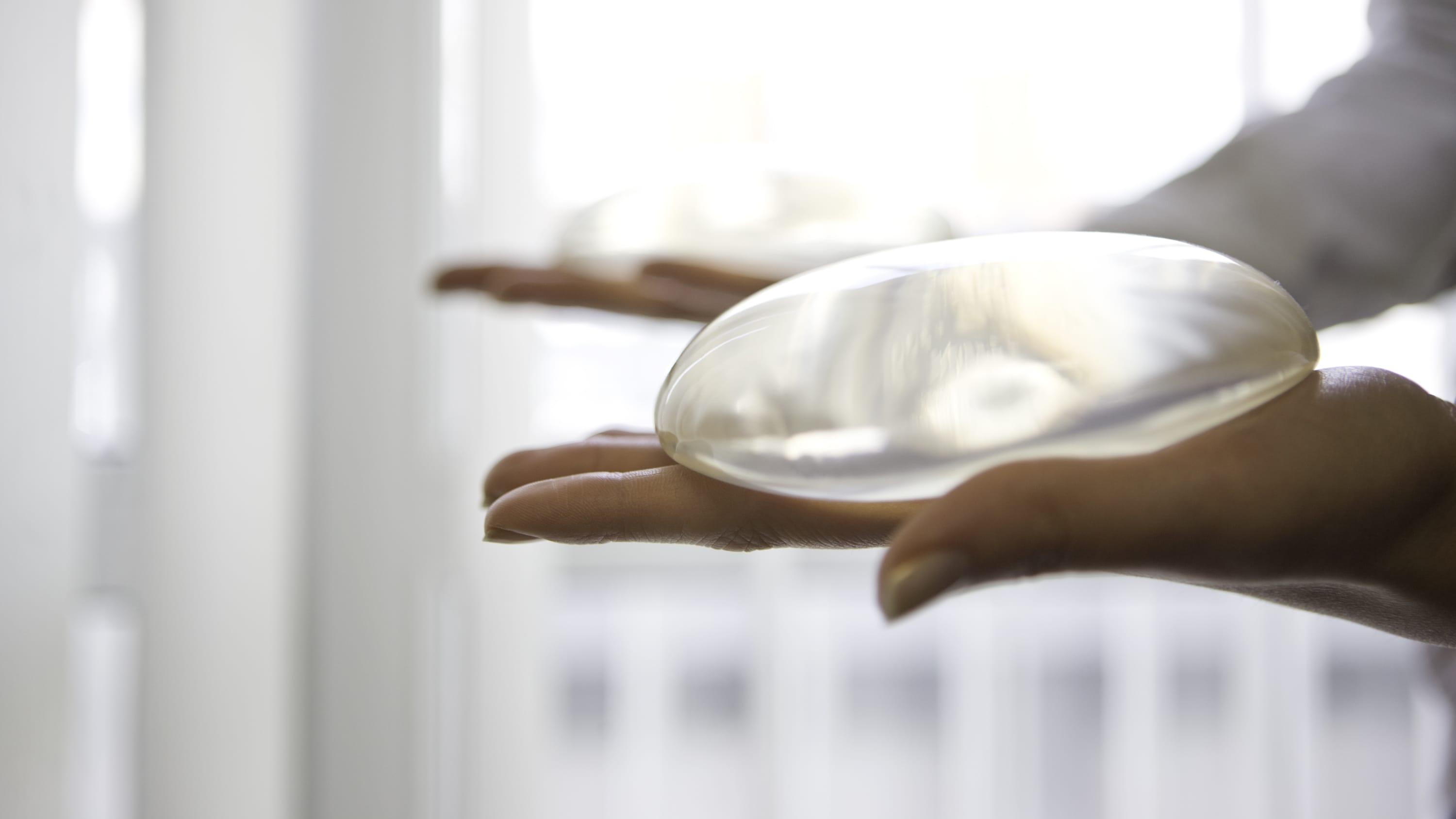 Hands holding a round, silicone breast implant.