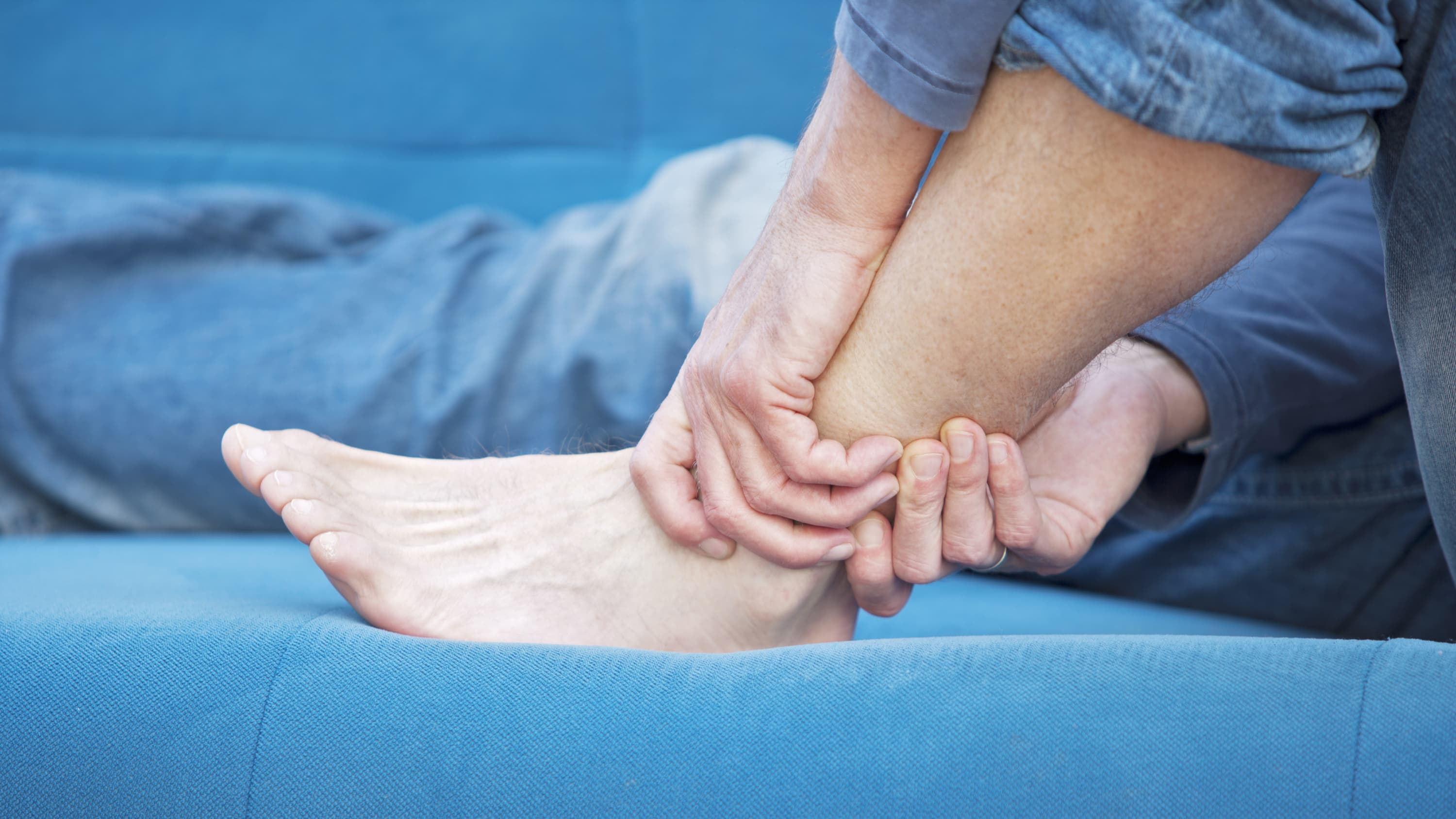 A man with lupus nephritis gripping his ankle on a blue couch.