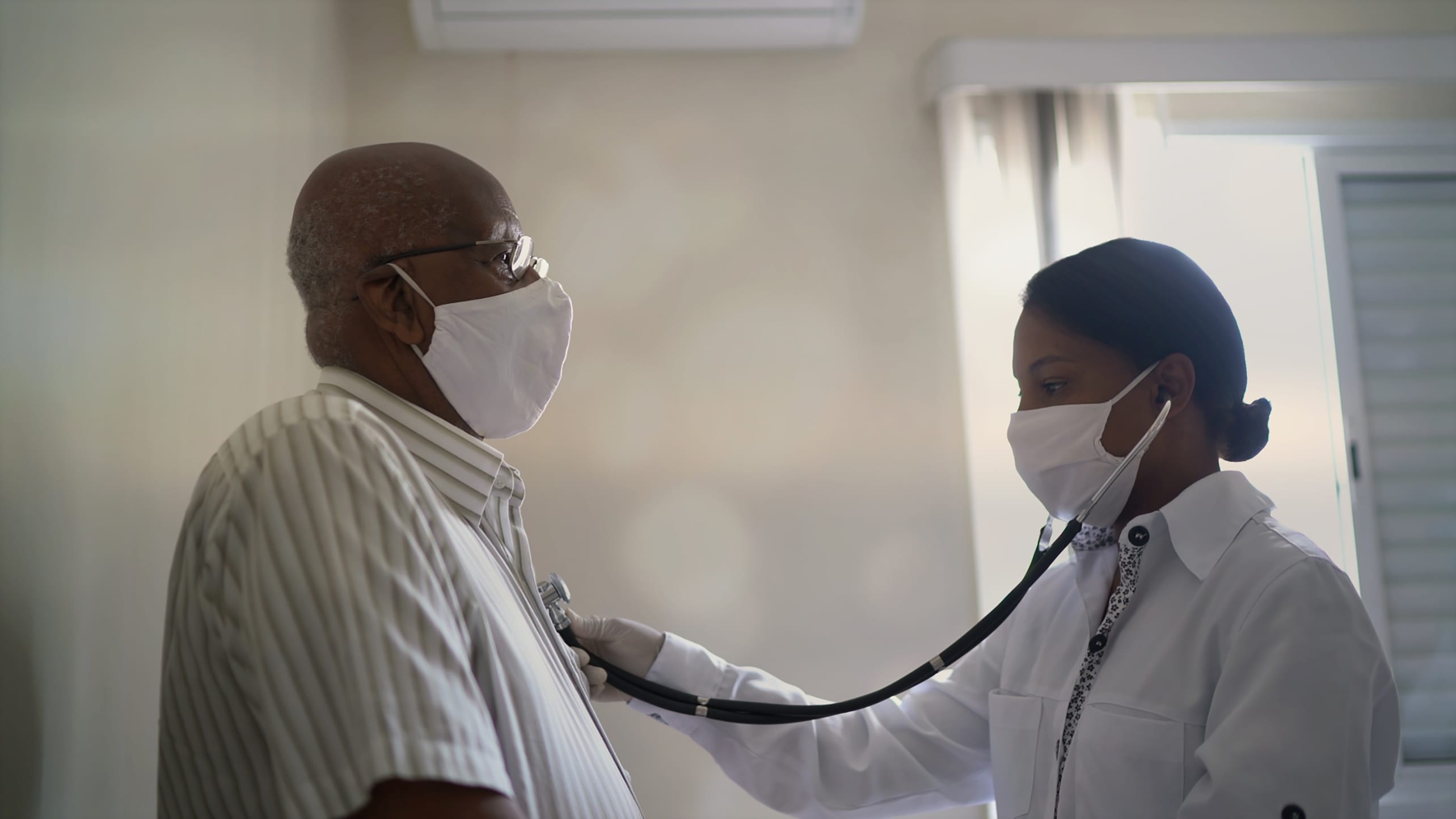 A masked doctor listens to a patient's heart.