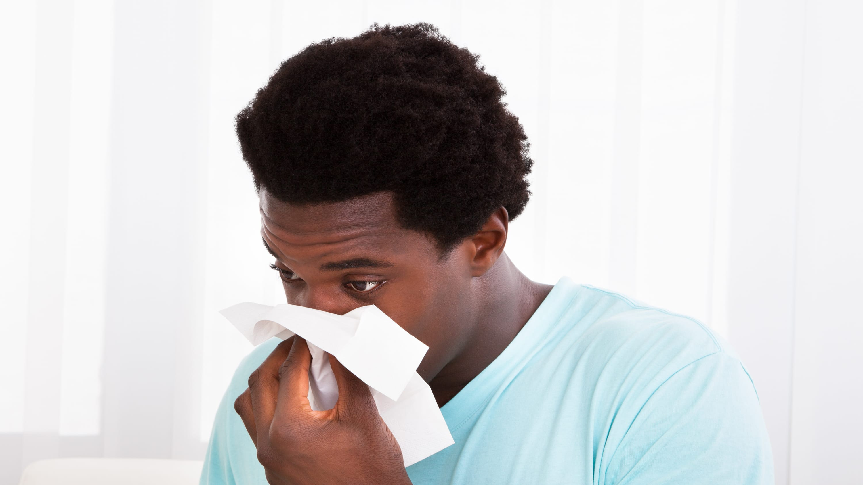 A man suffering from a cold blows his nose.
